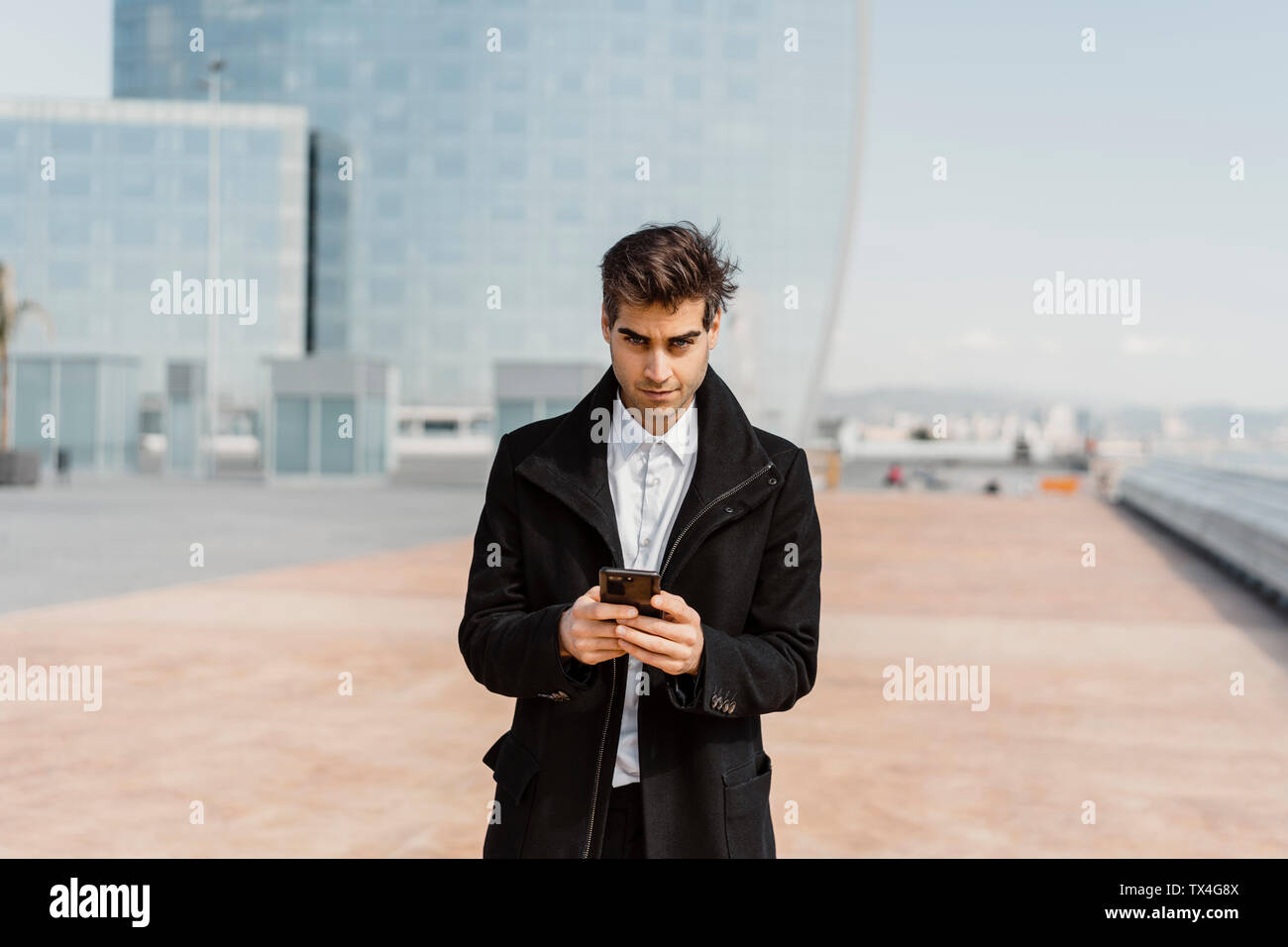 Portrait of businessman holding cell phone in the city - Stock Image