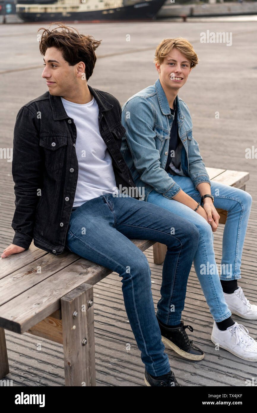 Denmark, Copenhagen, two young men sitting on a bench - Stock Image