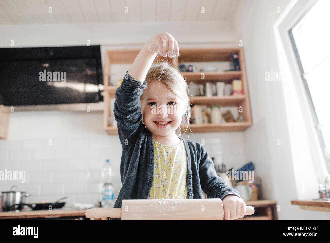 Portrait of smilingl ittle girl rolling out dough in the kitchen Stock Photo