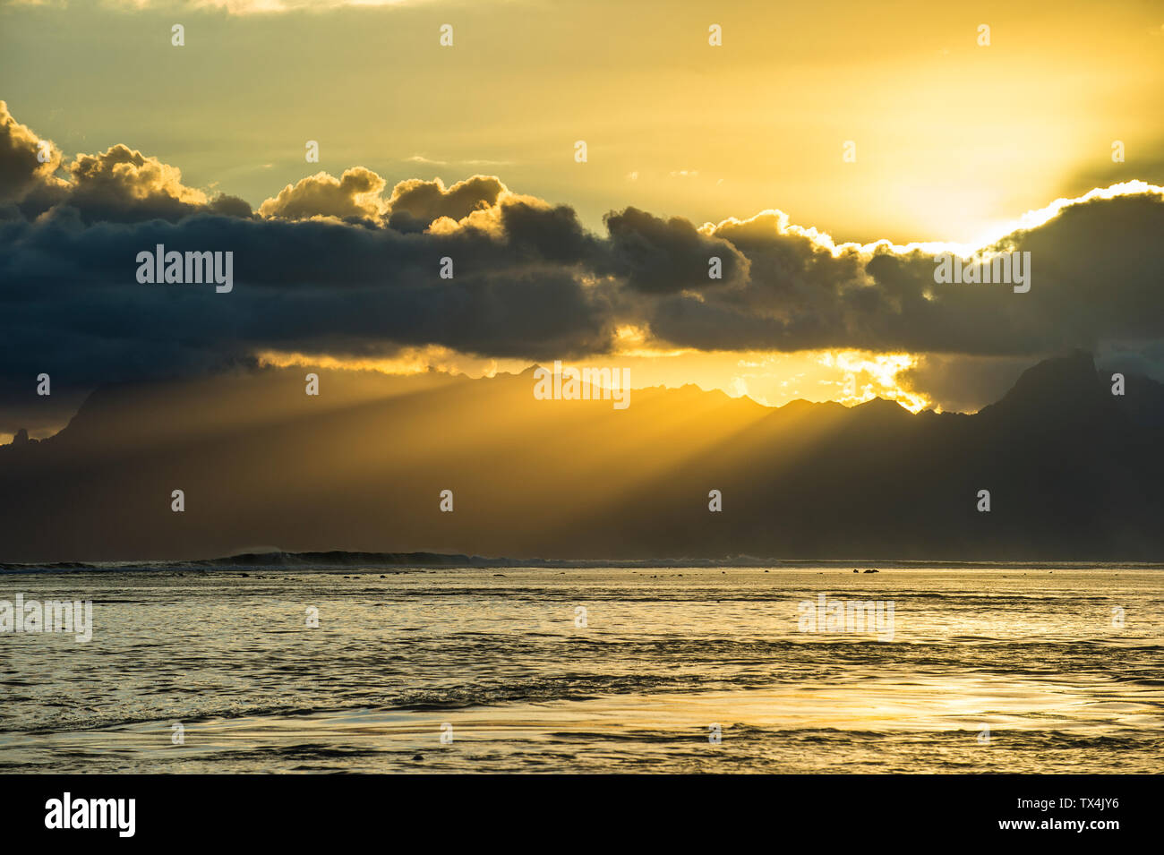 French Polynesia, Tahiti, sunrays breaking through the clouds over Moorea Stock Photo
