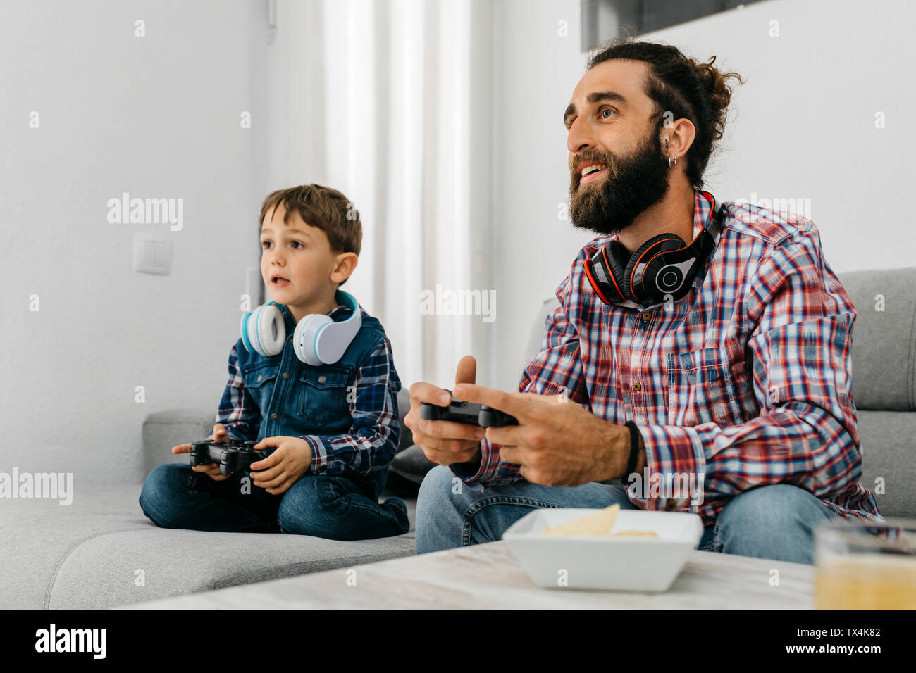 Portrait of father and son sitting together on the couch playing computer game Stock Photo