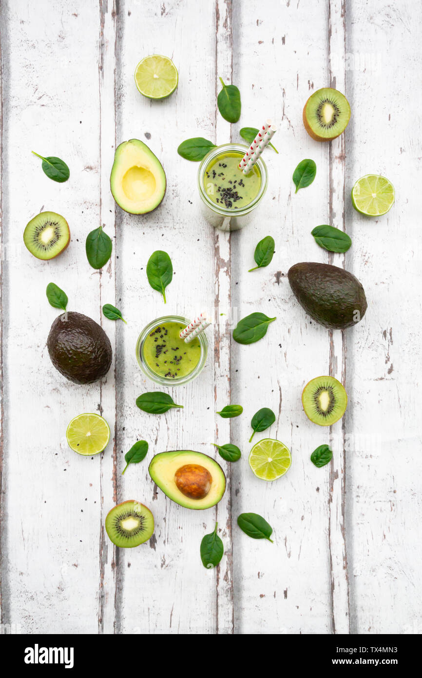 Two glasses of green smoothie with avocado, spinach, kiwi and lime - Stock Image