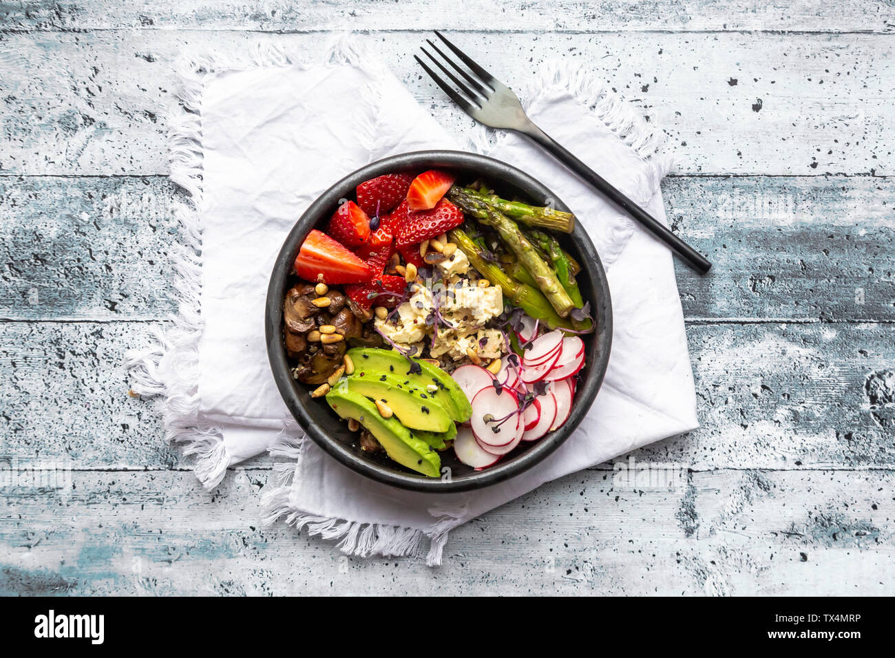 Veggie bowl with quinoa, vegetables, feta, strawberries, avocado, pine nuts and cress - Stock Image