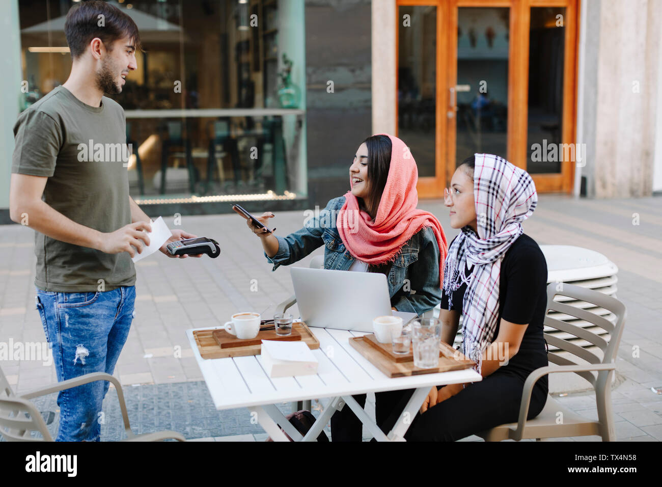 Young woman paying cashless with smartphone in a cafe - Stock Image
