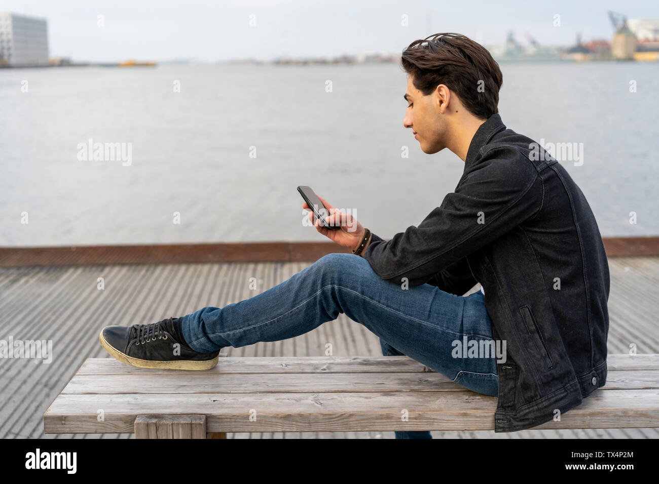 Denmark, Copenhagen, young man sitting on a bench at the waterfront using cell phone - Stock Image