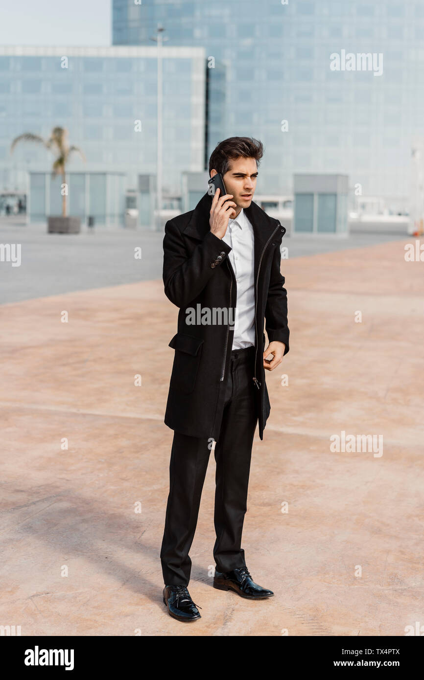 Businessman talking on cell phone in the city - Stock Image
