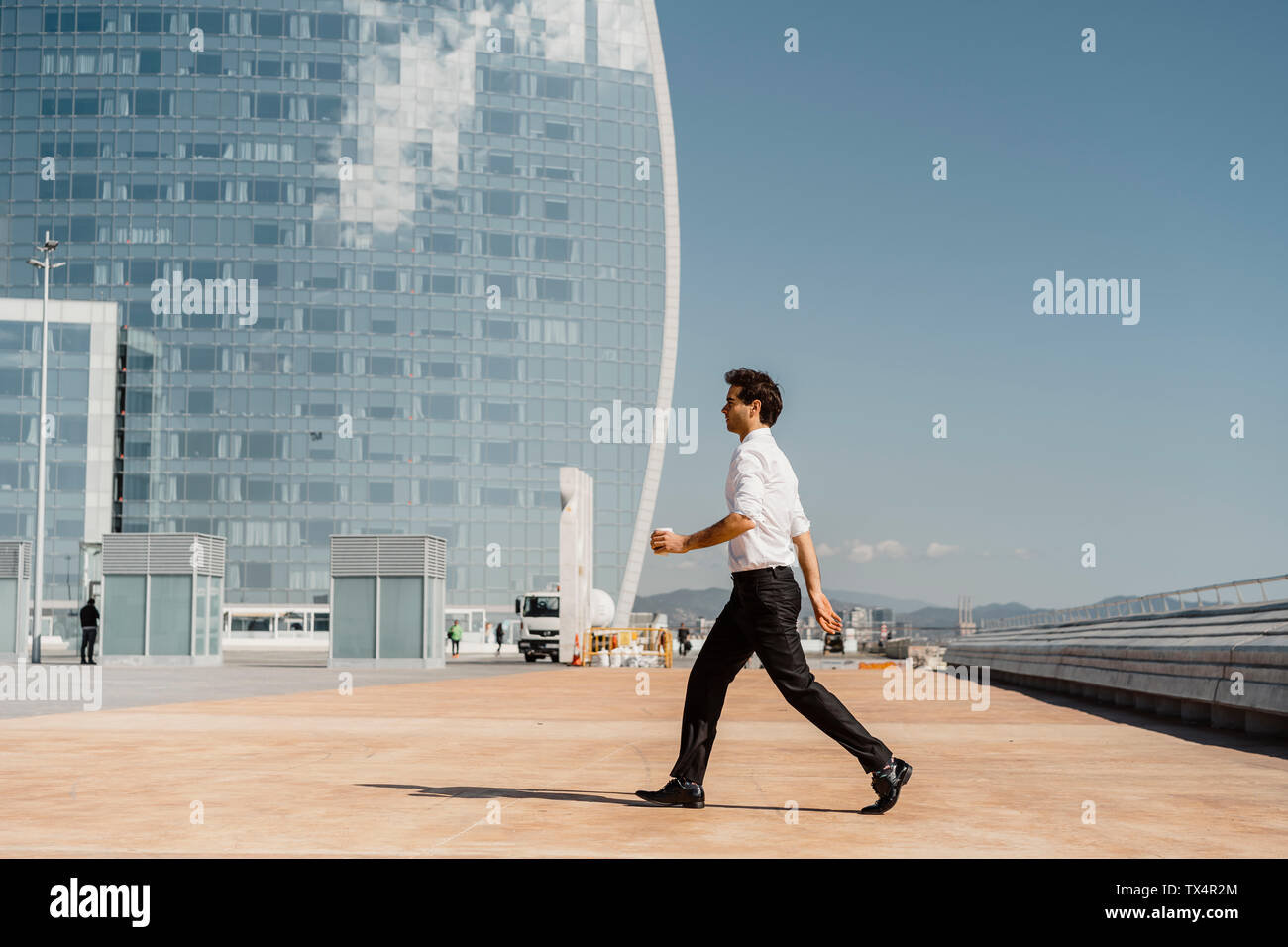 Businessman with takeaway coffee walking in the city - Stock Image