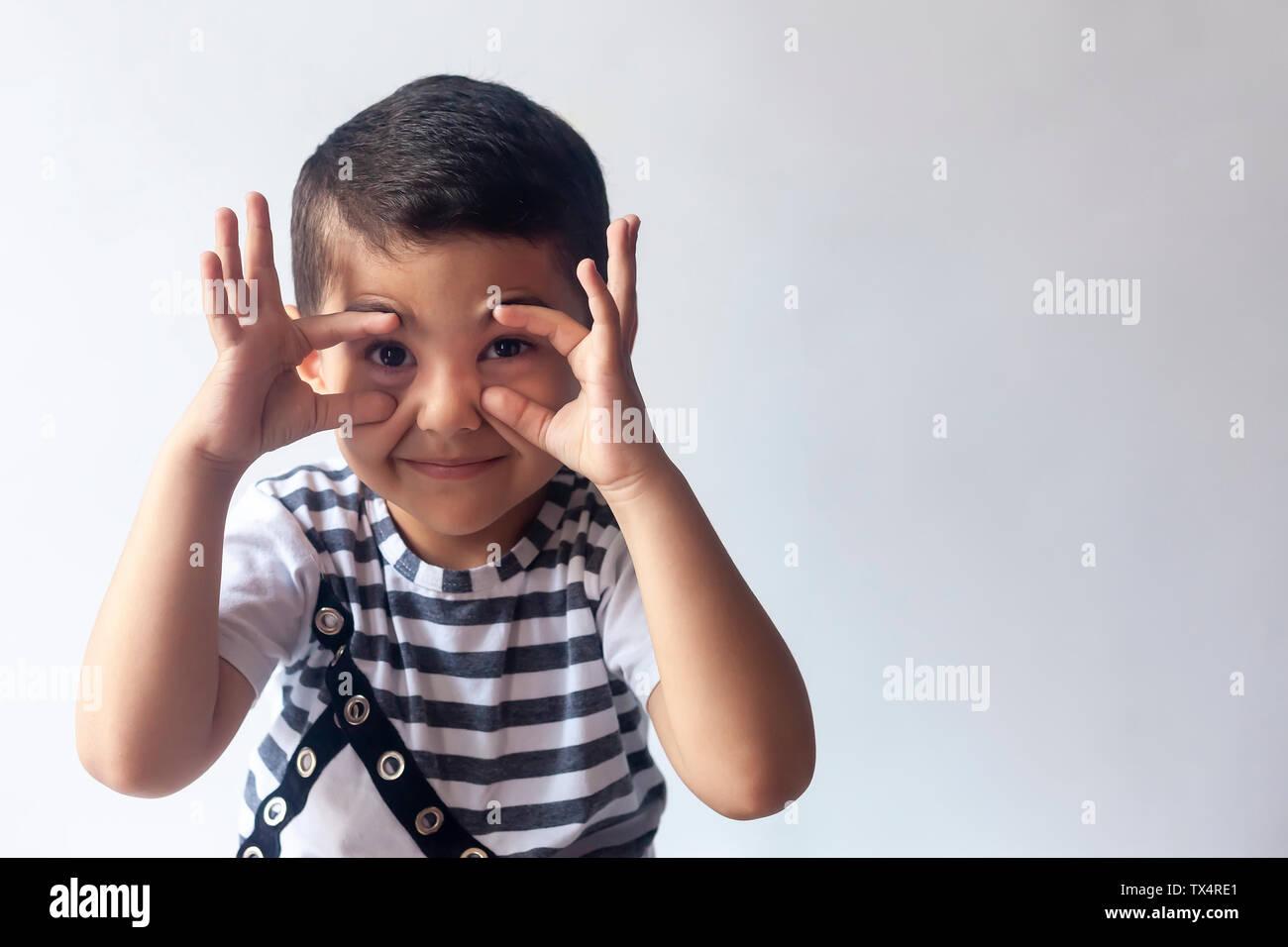 Six years boy portrait. Innocent smiling little boy on grey background. Little kid having fun. People, childhood lifestyle concept. Stock Photo