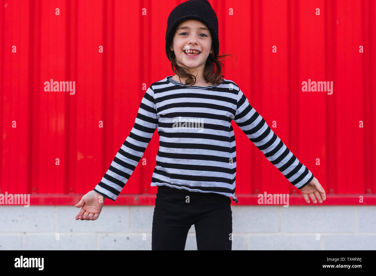 Portrait of happy little girl wearing striped shirt and black cap Stock Photo