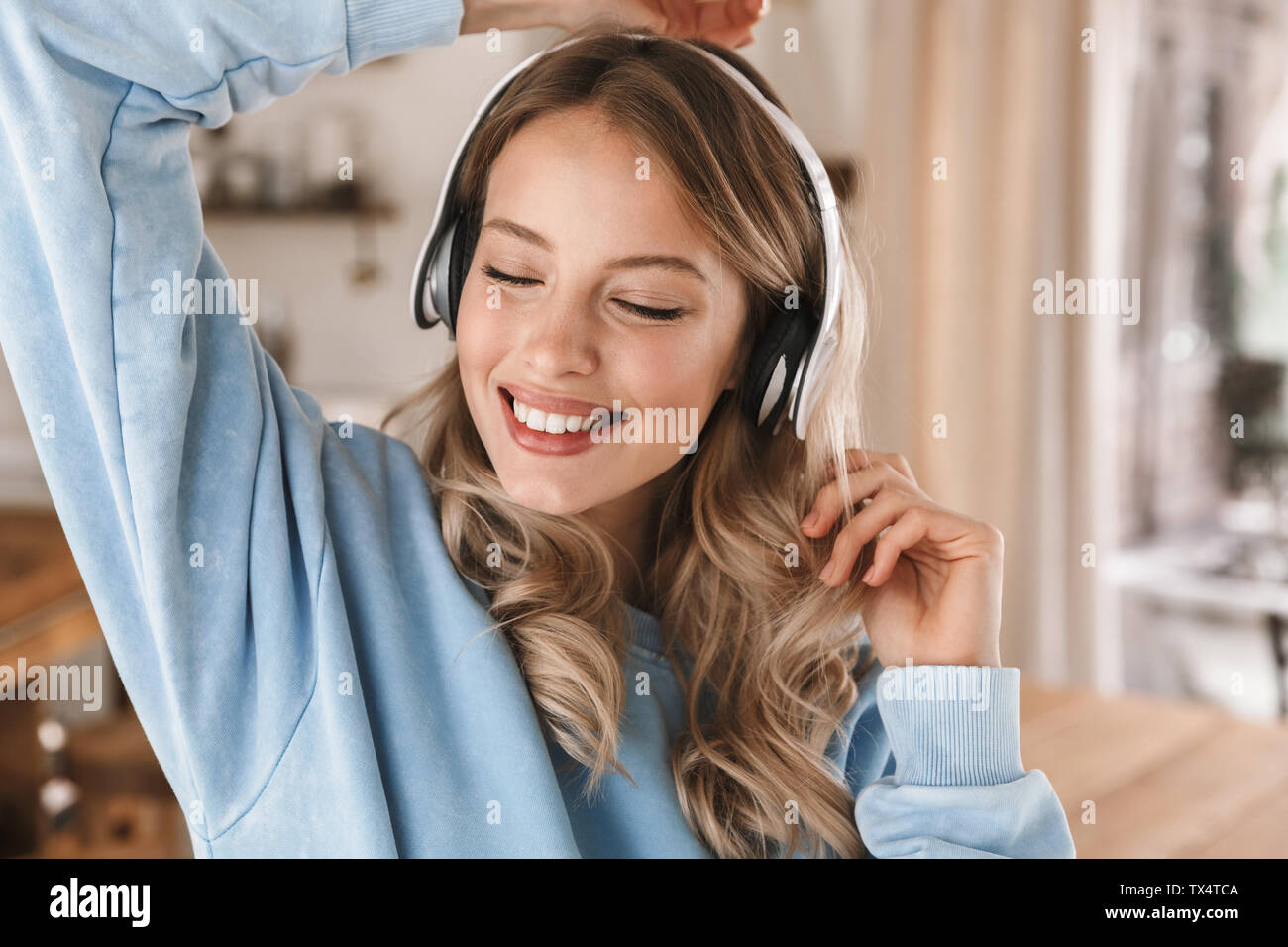 Portrait of pretty blond girl 20s wearing headphones smiling and rejoicing while listening to music at home Stock Photo