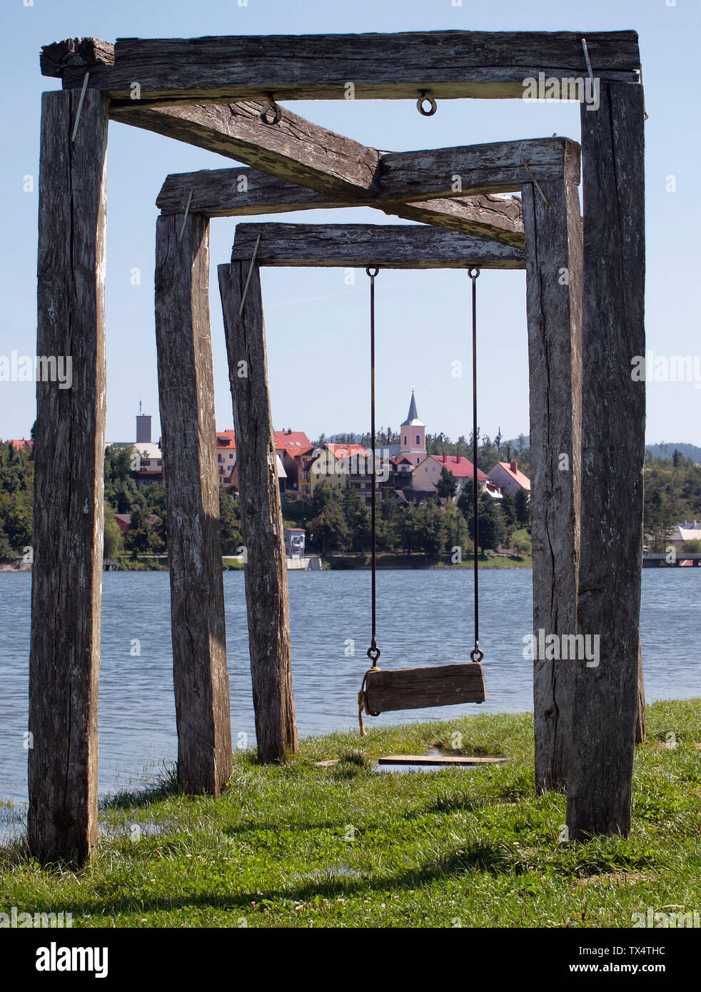 Wooden swing with lake bajer and Fužine town in background Stock Photo