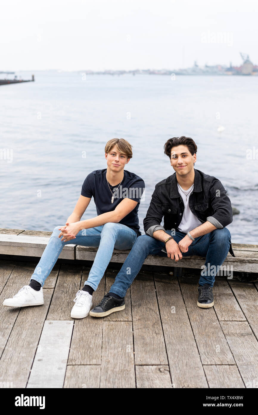 Denmark, Copenhagen, portrait of two confident young men sitting at the waterfront - Stock Image