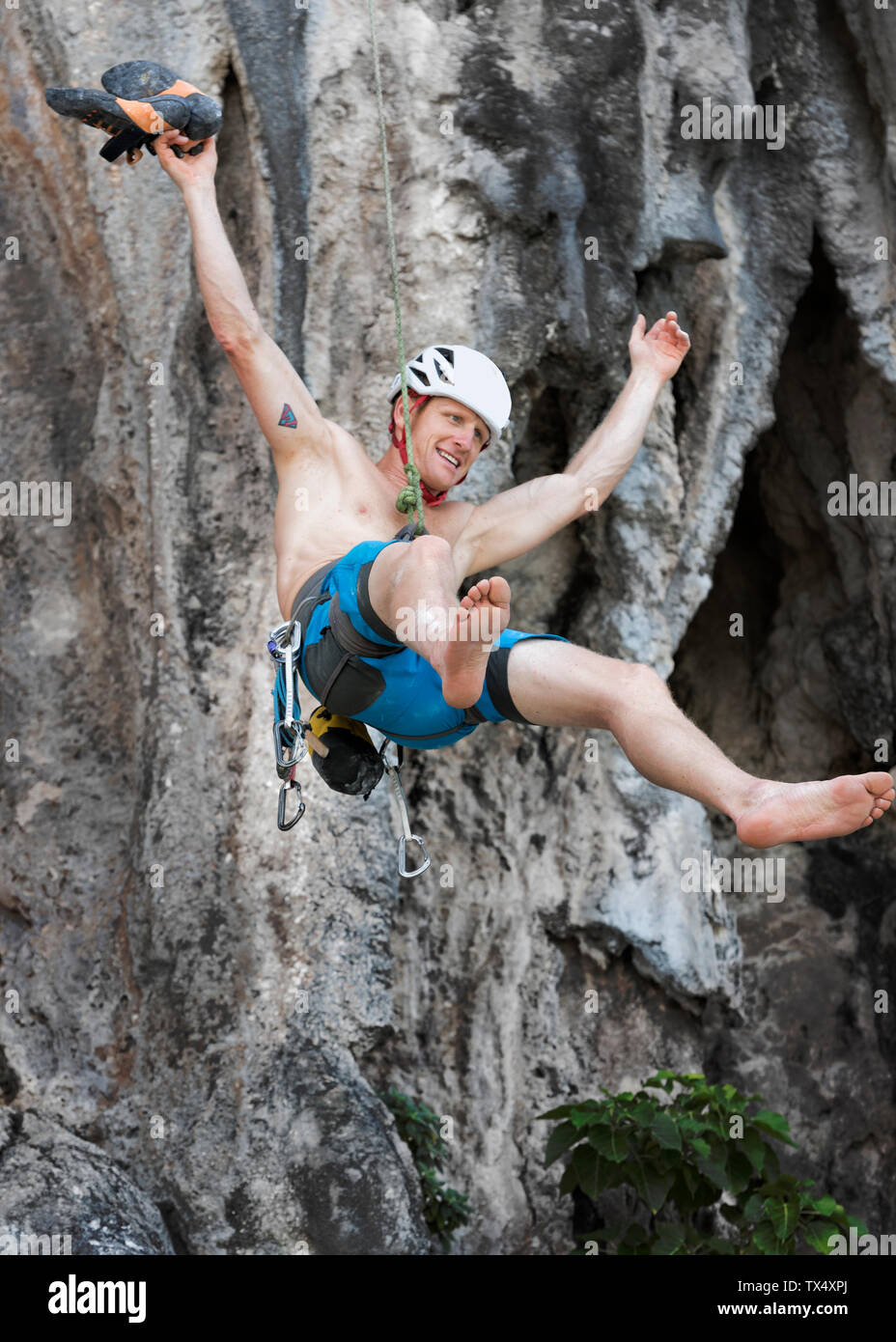 Thailand, Krabi, Lao Liang, barechested climber abseiling from rock wall Stock Photo