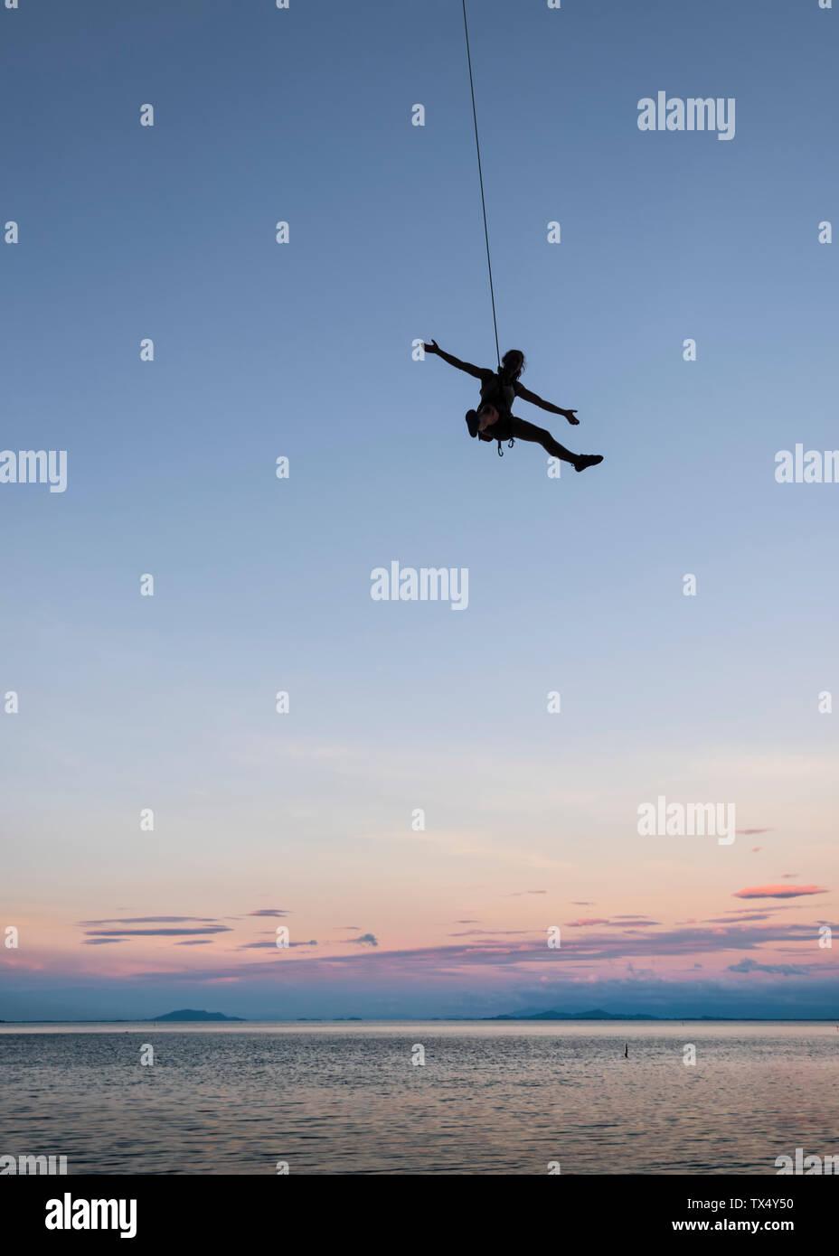 Thailand, Krabi, Lao Liang island, climber abseiling above the sea Stock Photo