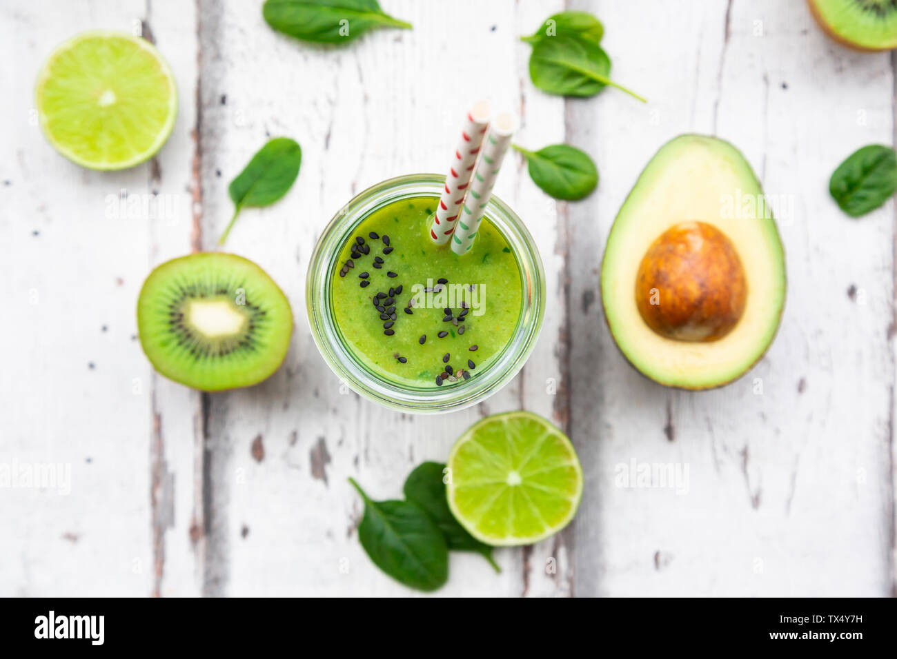 Glass of green smoothie with avocado, spinach, kiwi and lime - Stock Image