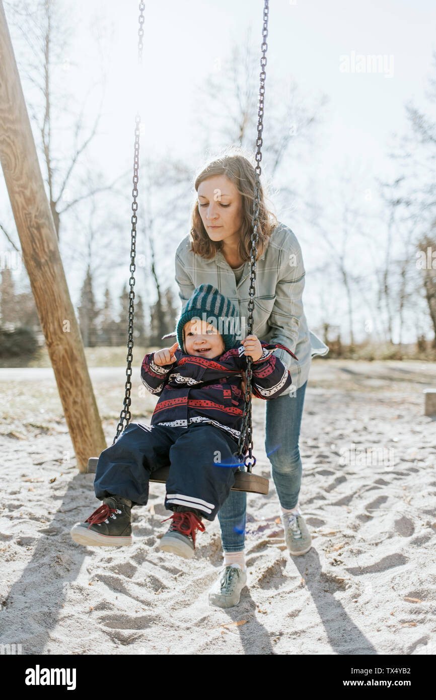 Mother with little daughter on swing on a playground Stock Photo