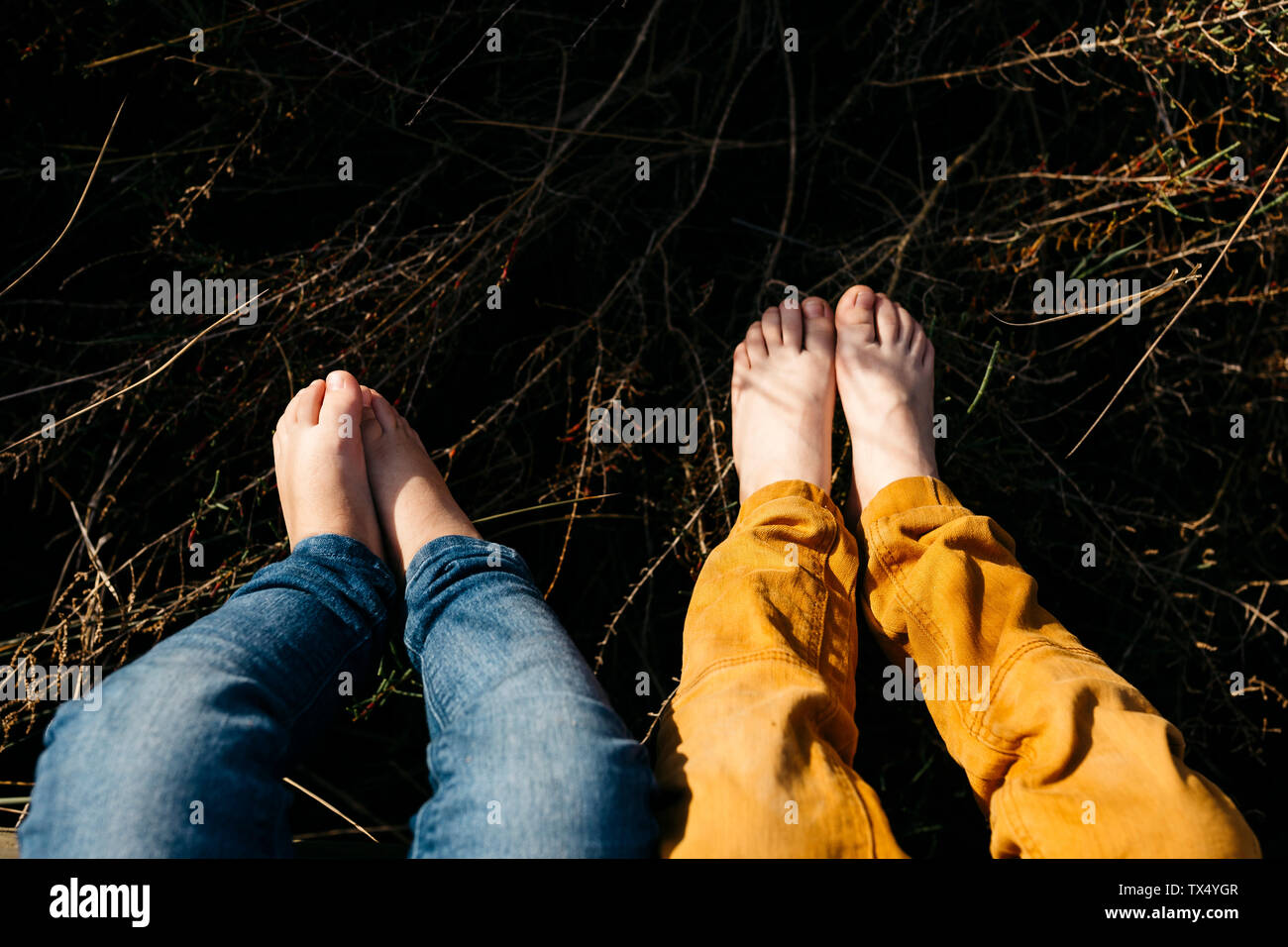 Feet of little girl and her older brother in nature, close-up Stock Photo