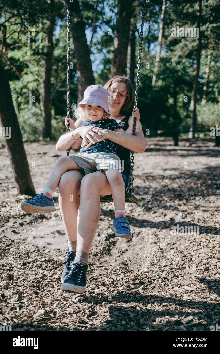 Happy mother with little daughter on swing on a playground Stock Photo
