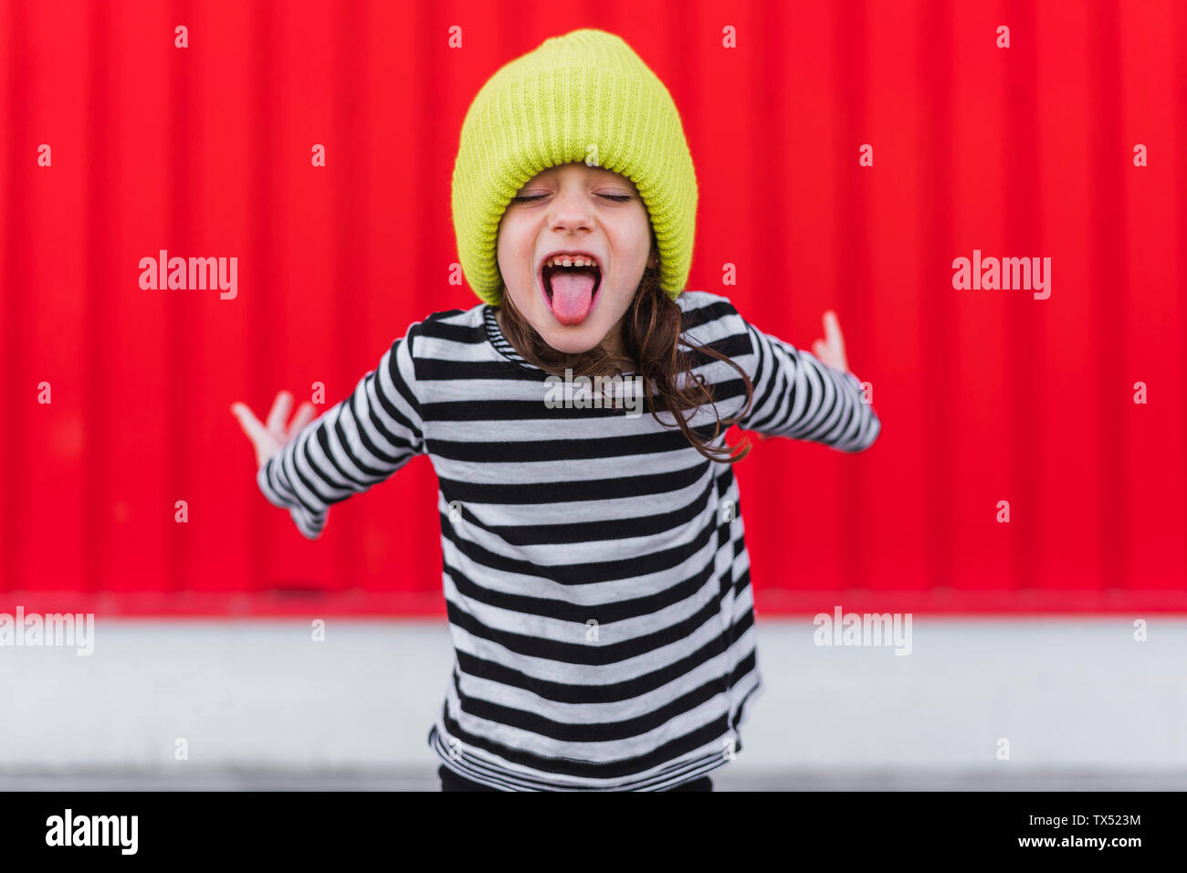 Portrait of little girl wearing striped shirt and yellow cap sticking out tongue in front of red background Stock Photo