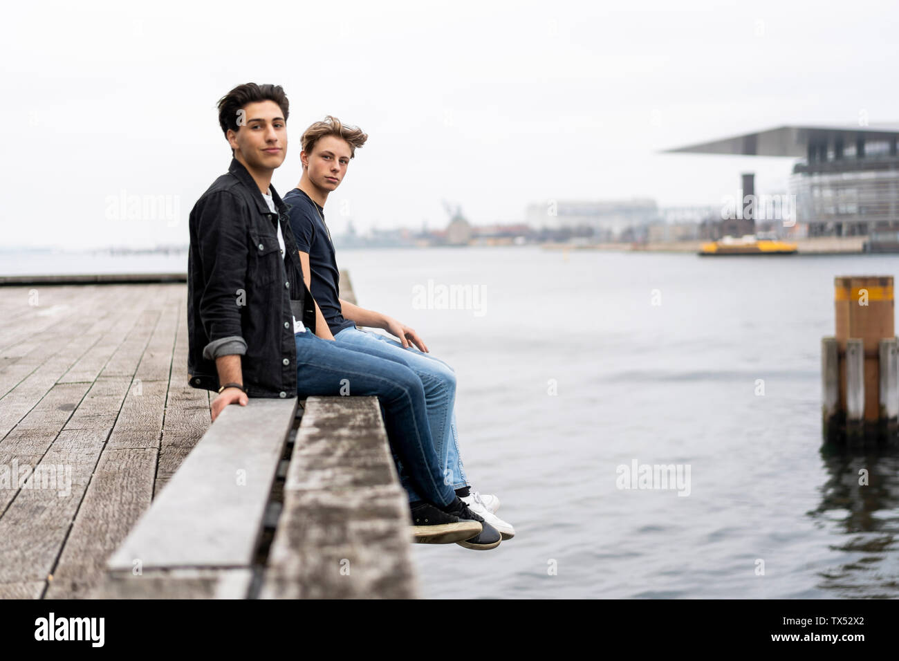 Denmark, Copenhagen, two young men sitting at the waterfront - Stock Image