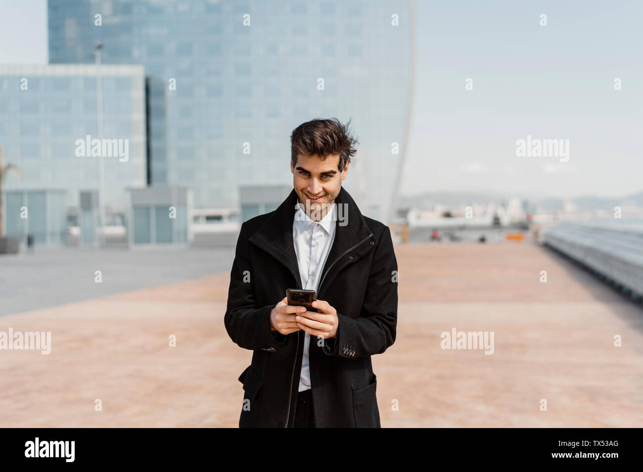 Portrait of smiling businessman holding cell phone in the city - Stock Image