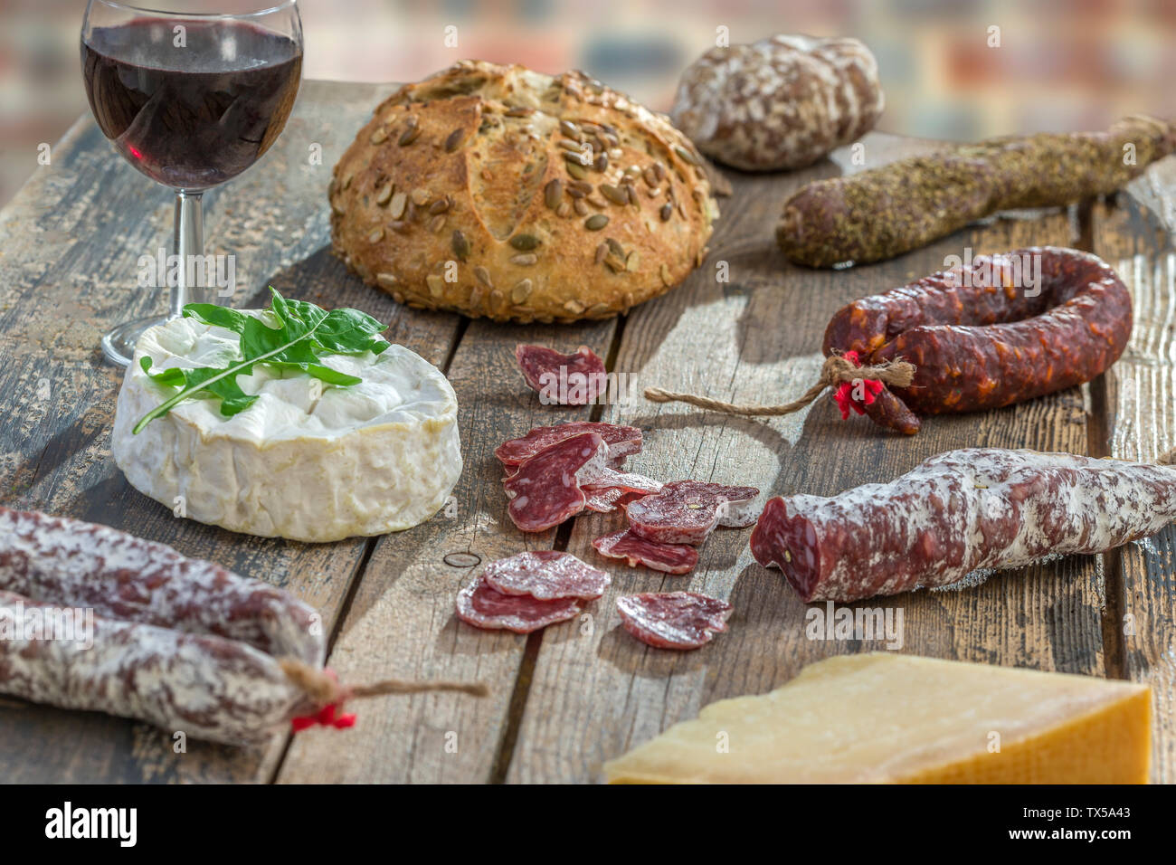 French snacks with wine - various types of cheeses, bread , dry saussages, charcuterie, red vine on a gray background. Top view. Stock Photo