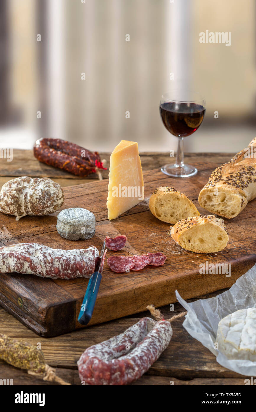 French snacks with wine - various types of cheeses, bread , dry saussages, charcuterie, red vine on a gray background. Stock Photo