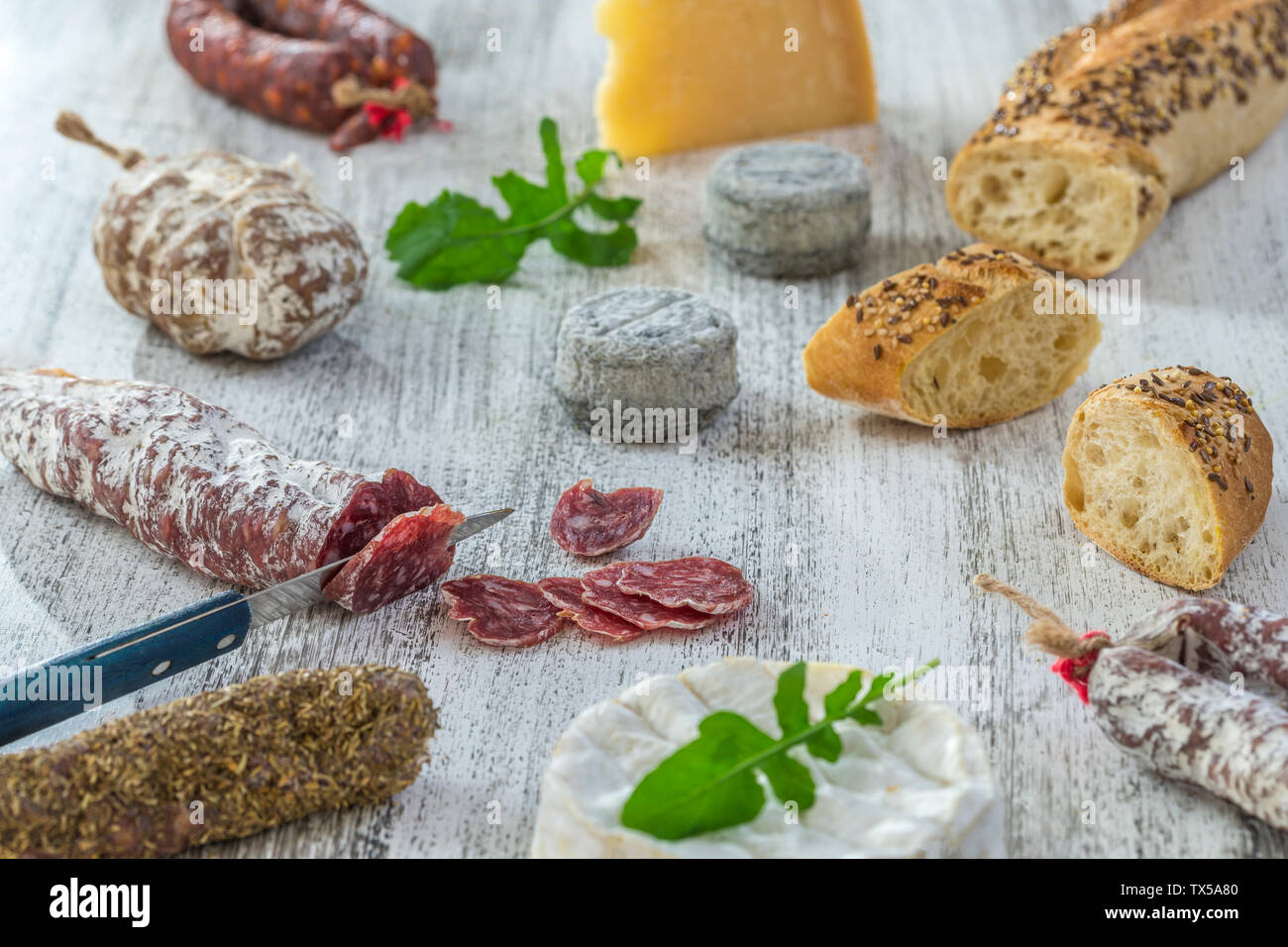 French snacks with wine - various types of cheeses, bread , dry saussages, charcuterie, red vine on a gray background. Top view. Food background Stock Photo