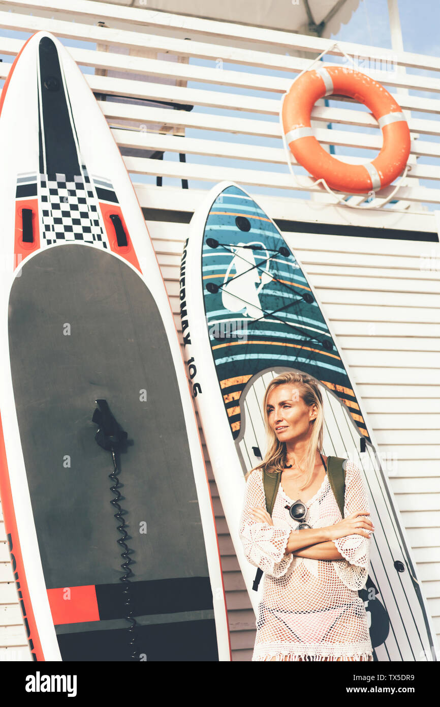 Portrait of a surfer with SUP boards near by white wooden wall. Young blonde woman with a stand up paddleboards. surfer lifestyle. - Stock Image