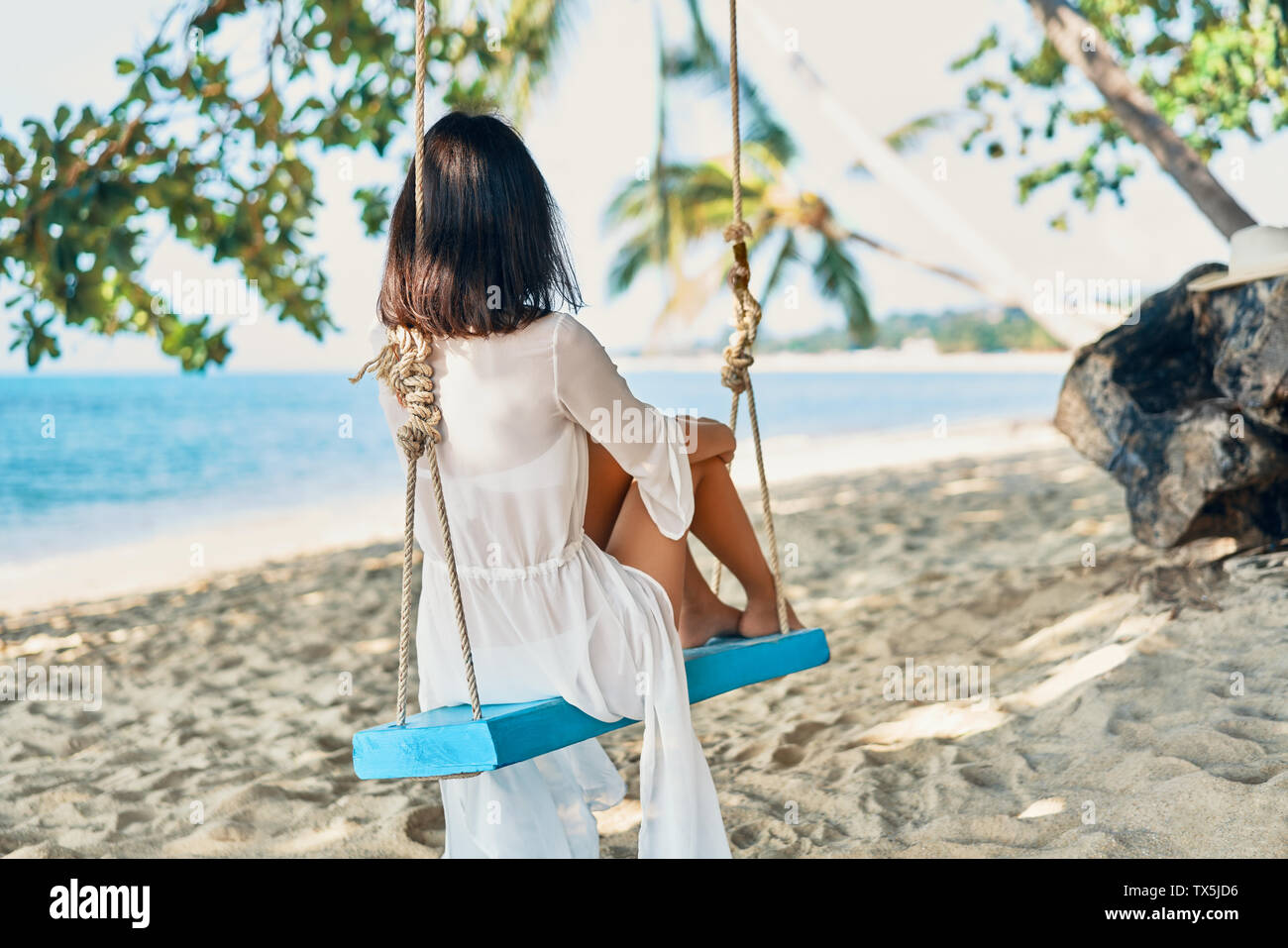Back view of happy woman relax on swing on beautiful paradises beach. Relax and vacation concept - Stock Image