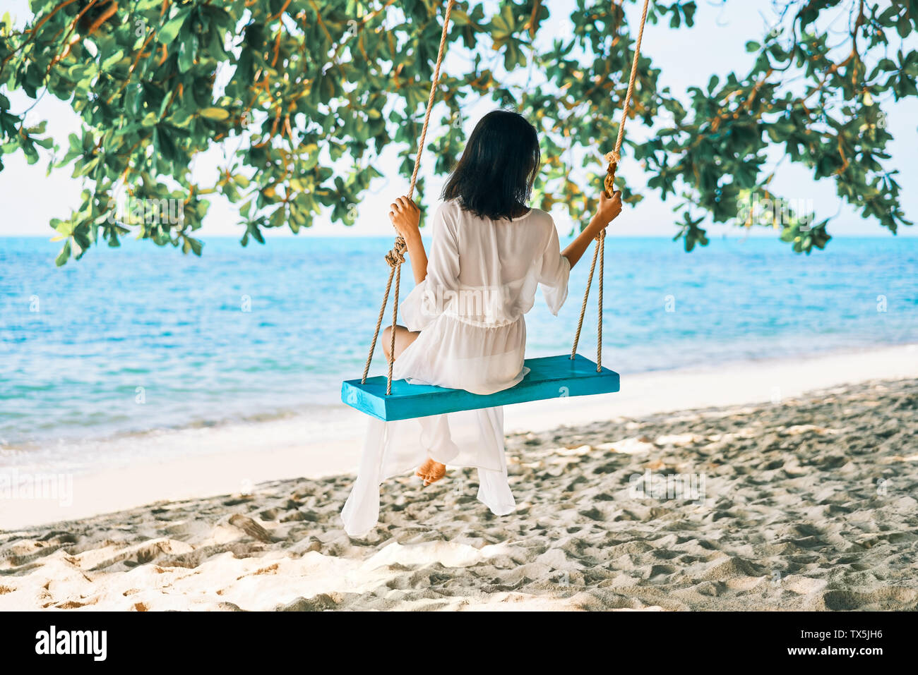 Carefree happy woman on swing on beautiful paradises beach. Relax and freedom concept - Stock Image