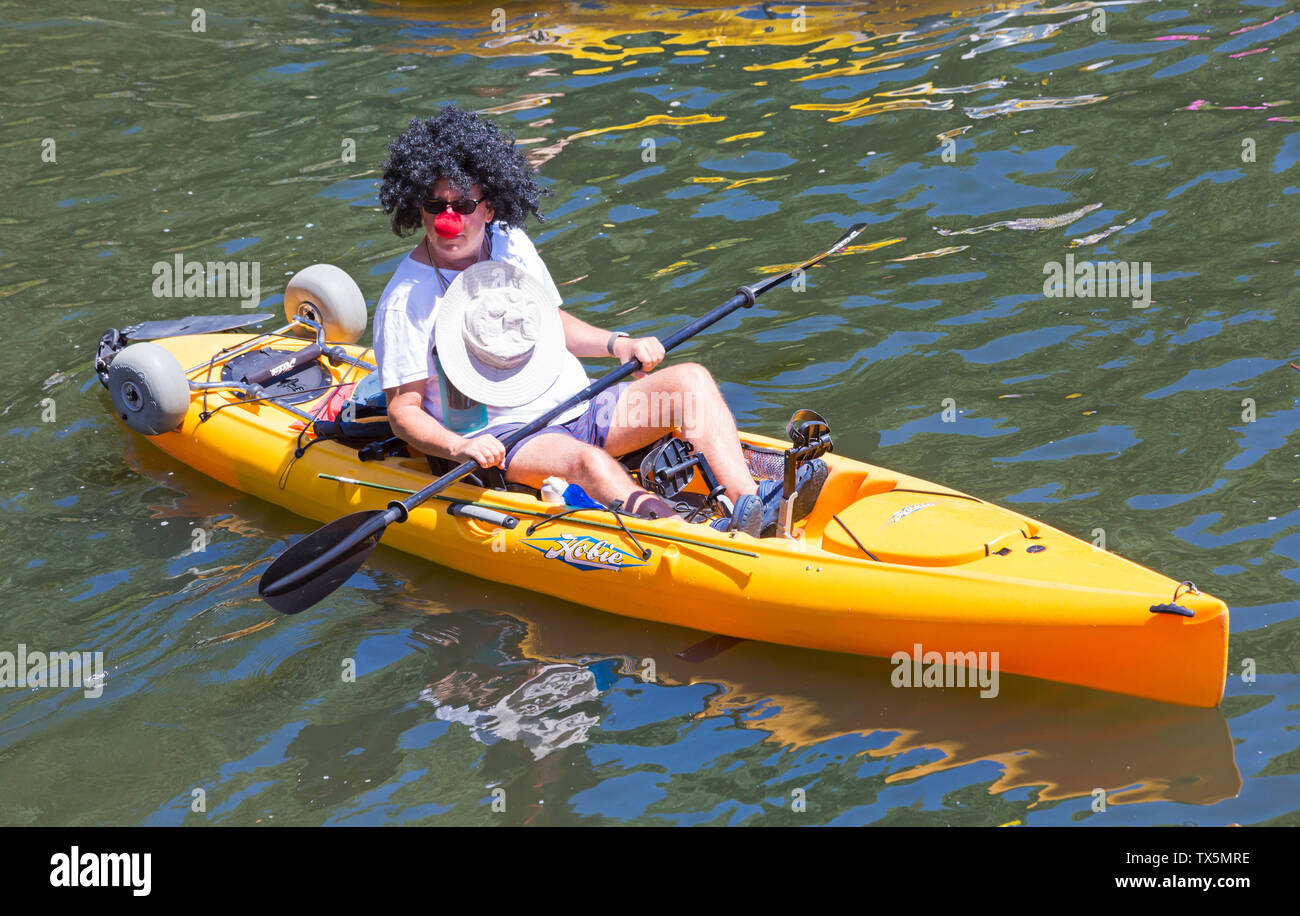 Man wearing wig and red nose in Hobie kayak having fun on Dorset Dinghy Day on River Stour, Iford, Dorset UK in June Stock Photo