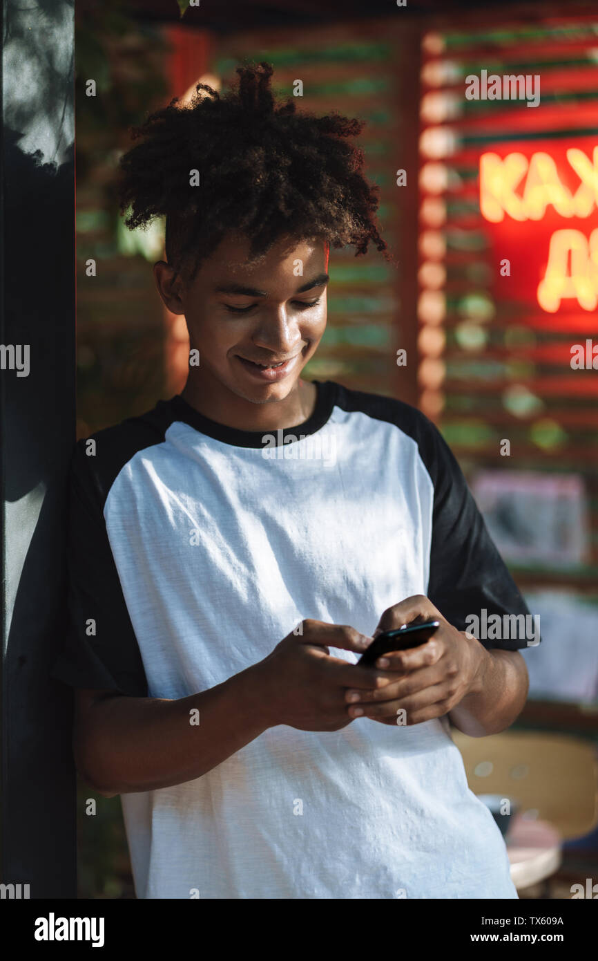 Smiling african young man using mobile phone at the cafe indoors - Stock Image