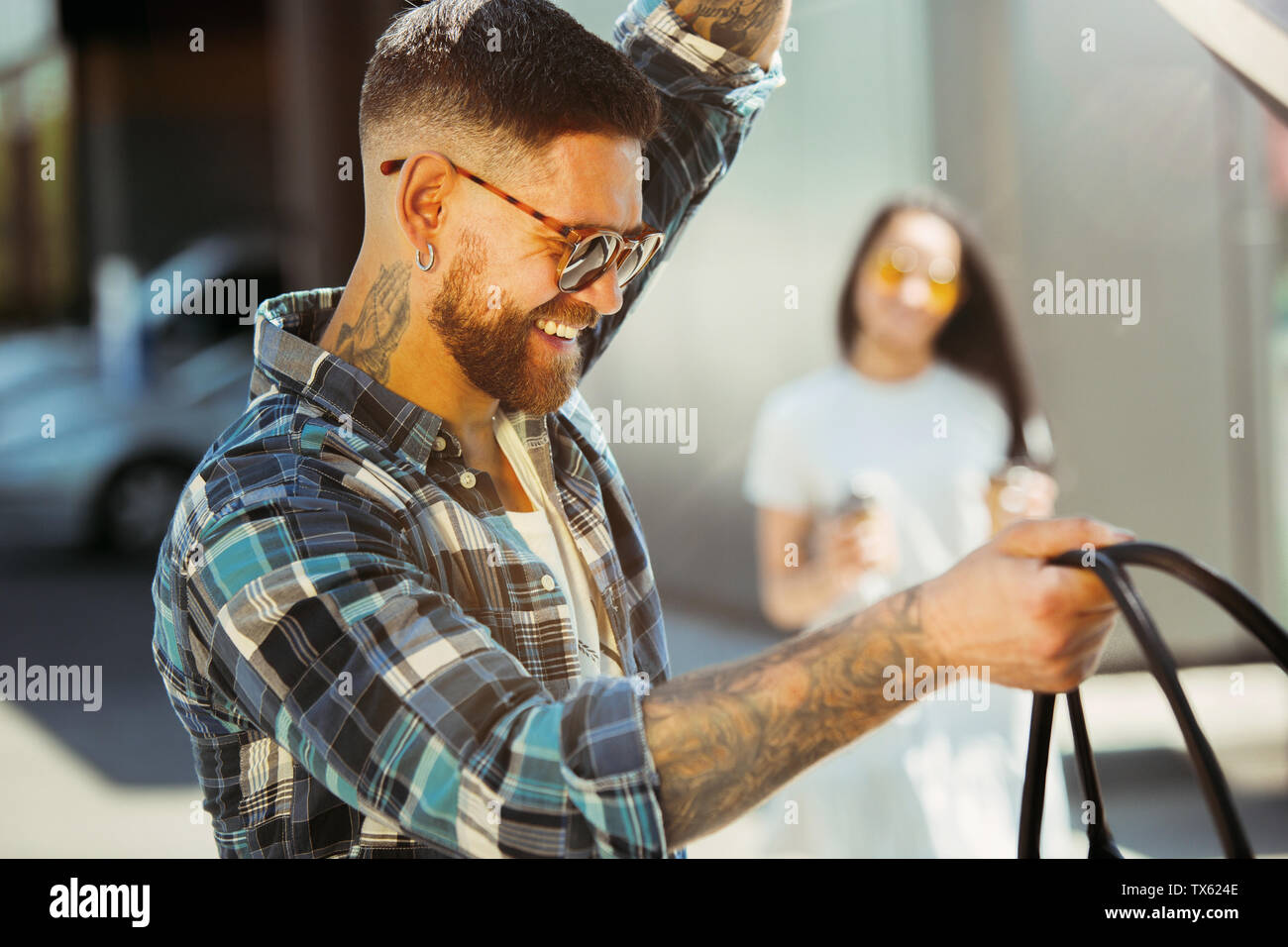 Young couple preparing for vacation trip on the car in sunny day. Woman and man shopping and ready for going to sea, riverside or ocean. Concept of relationship, vacation, summer, holiday, weekend. Stock Photo