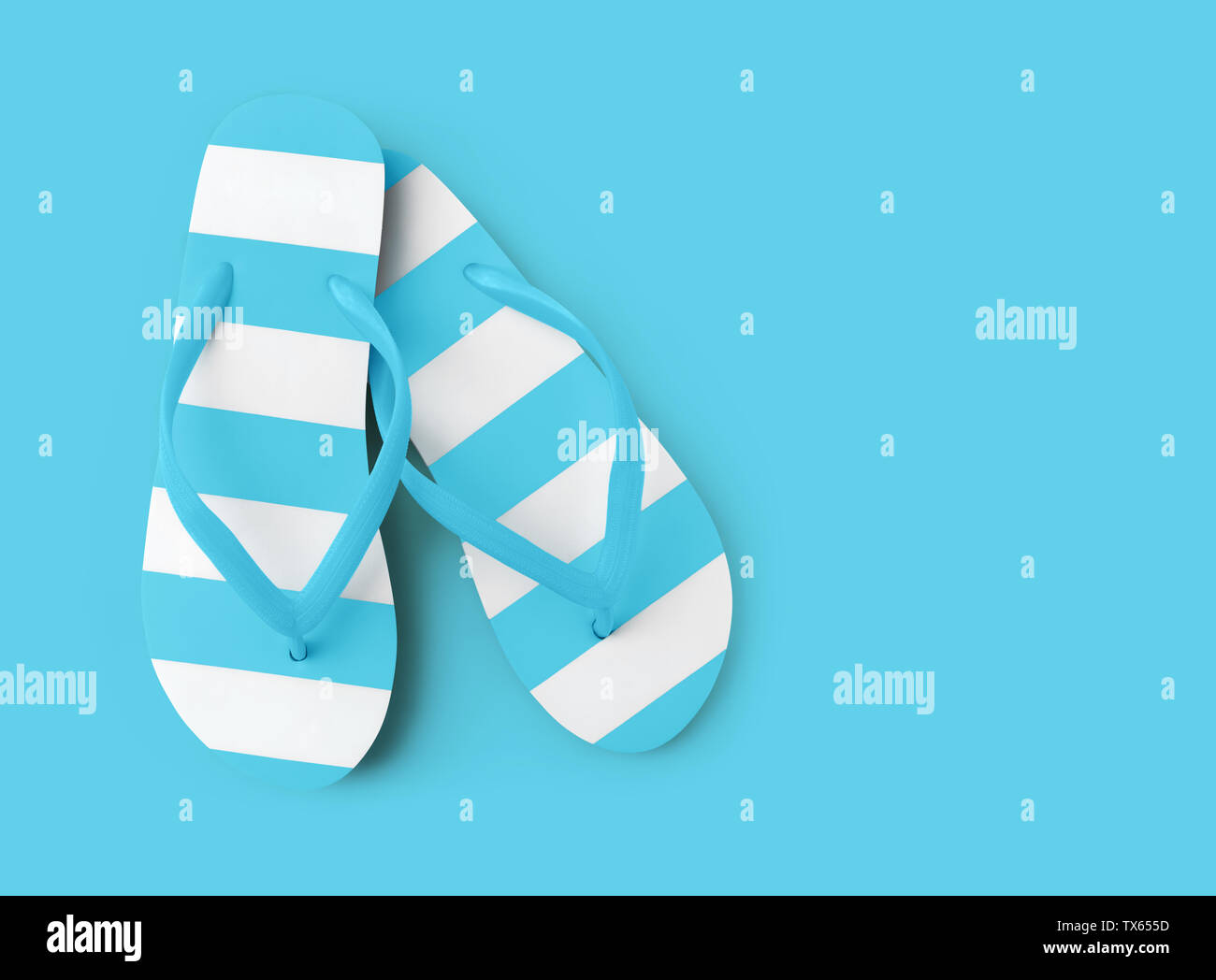 Top view of summer beach light blue flip flop on azure background sea holiday vacation and travel concept - Stock Image
