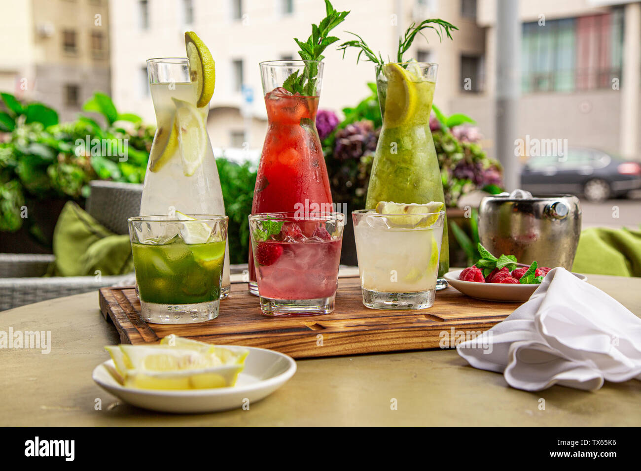 Summer soft drinks, a set of lemonades. Lemonades in jugs on the table, the ingredients of which they are made are arranged around. Stock Photo