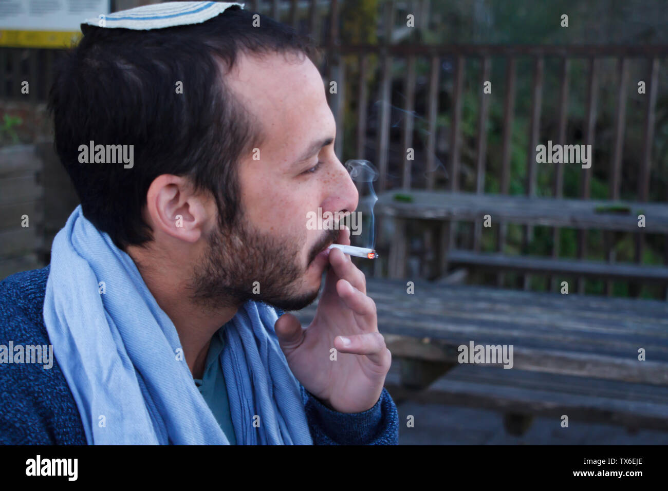 Naples, Italy - November 09, 2018: Profile of a young Jewish man in a traditional Jewish Kippa headdress talking, smiling, smoking on top of Mount Ves - Stock Image