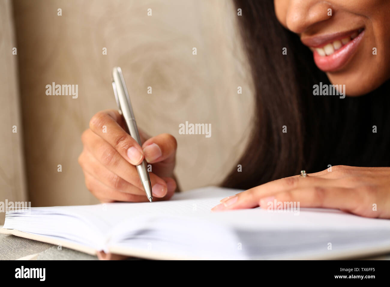 Arm of black woman write story in notebook preparing for college - Stock Image