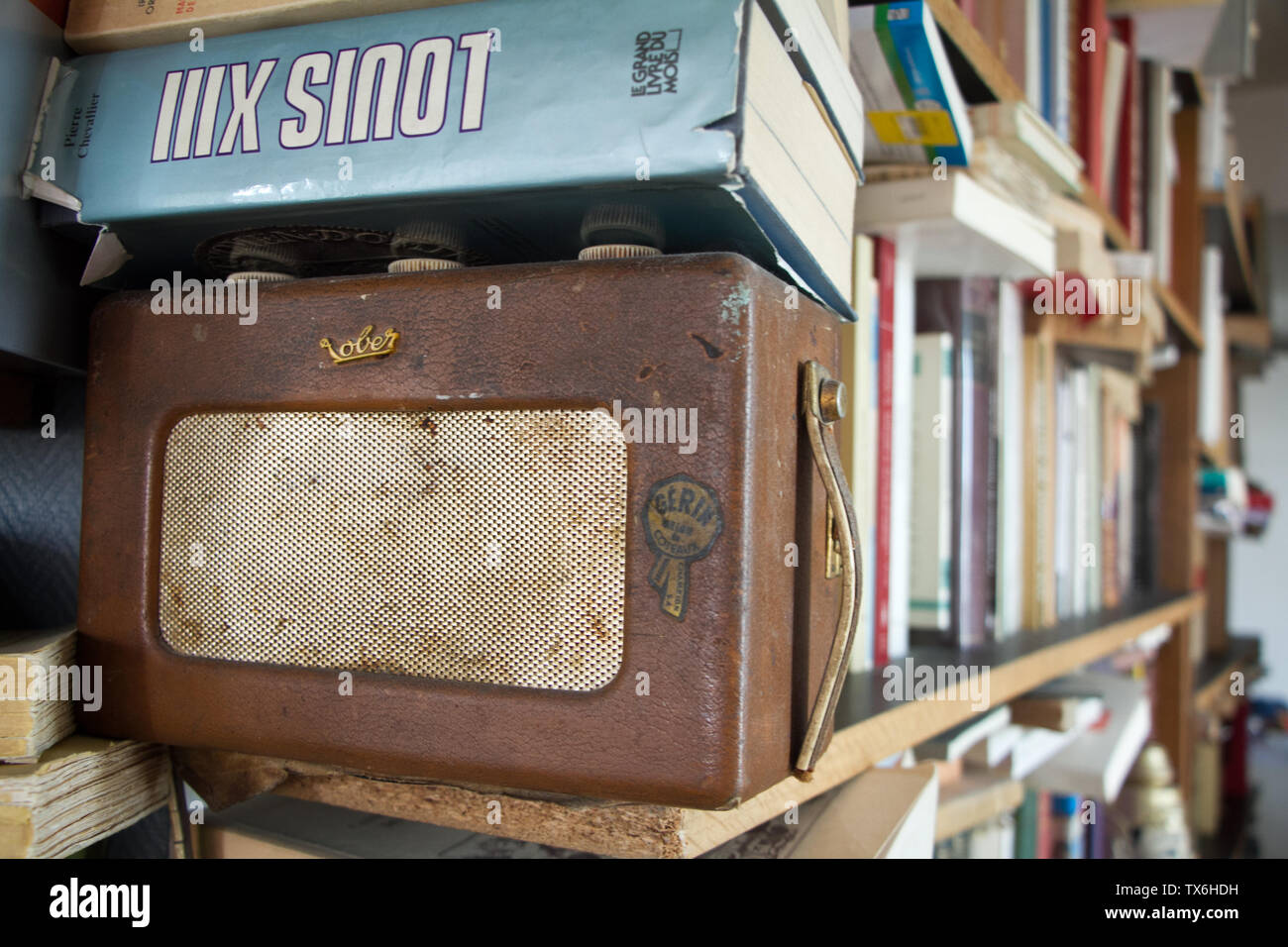 Paris, France - July 05, 2018: Closeup of a shelf with books and an old radio in a small apartment in the suburbs of Paris - Stock Image