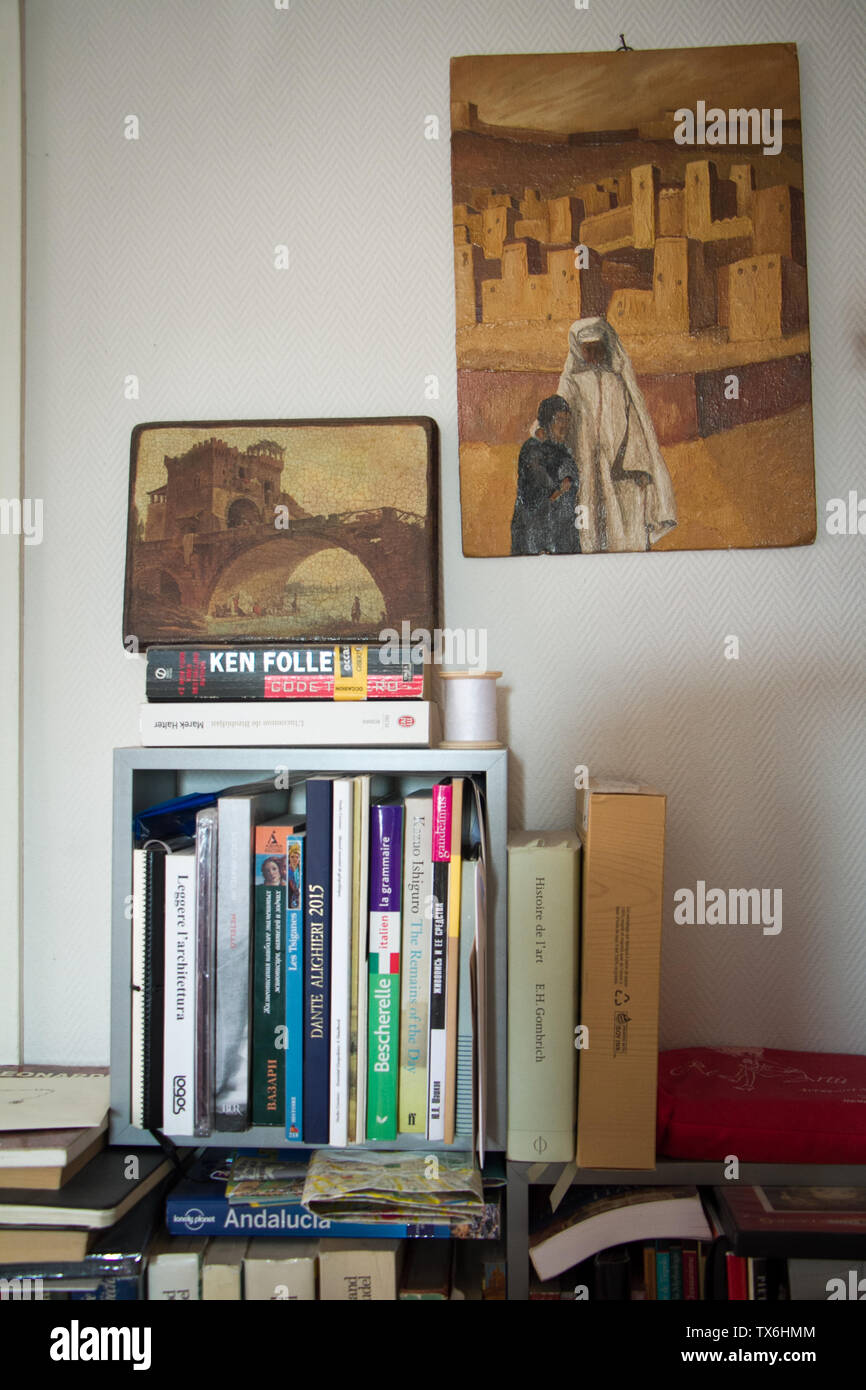 Paris, France - July 05, 2018: A shelf with books on a white wall and two paintings with architectural images in a small apartment in the suburbs of P - Stock Image
