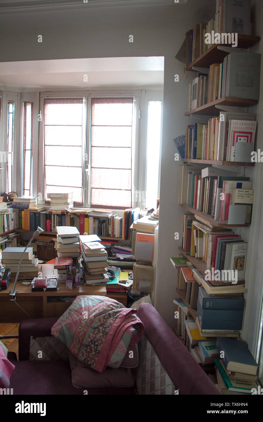Paris, France - July 05, 2018: Home library with a huge number of books and a window with shutters in a small apartment in the suburbs of Paris - Stock Image