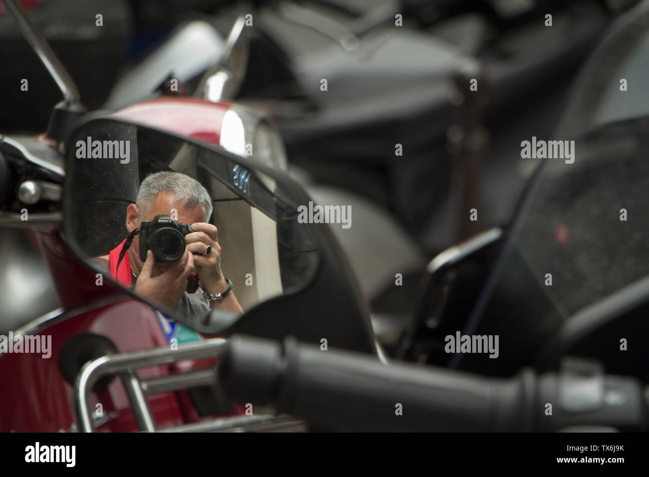 Paris, France - July 05, 2018: A photographer takes his selfie in the rearview mirror of a motorcycle parked on a street in Paris. Stock Photo