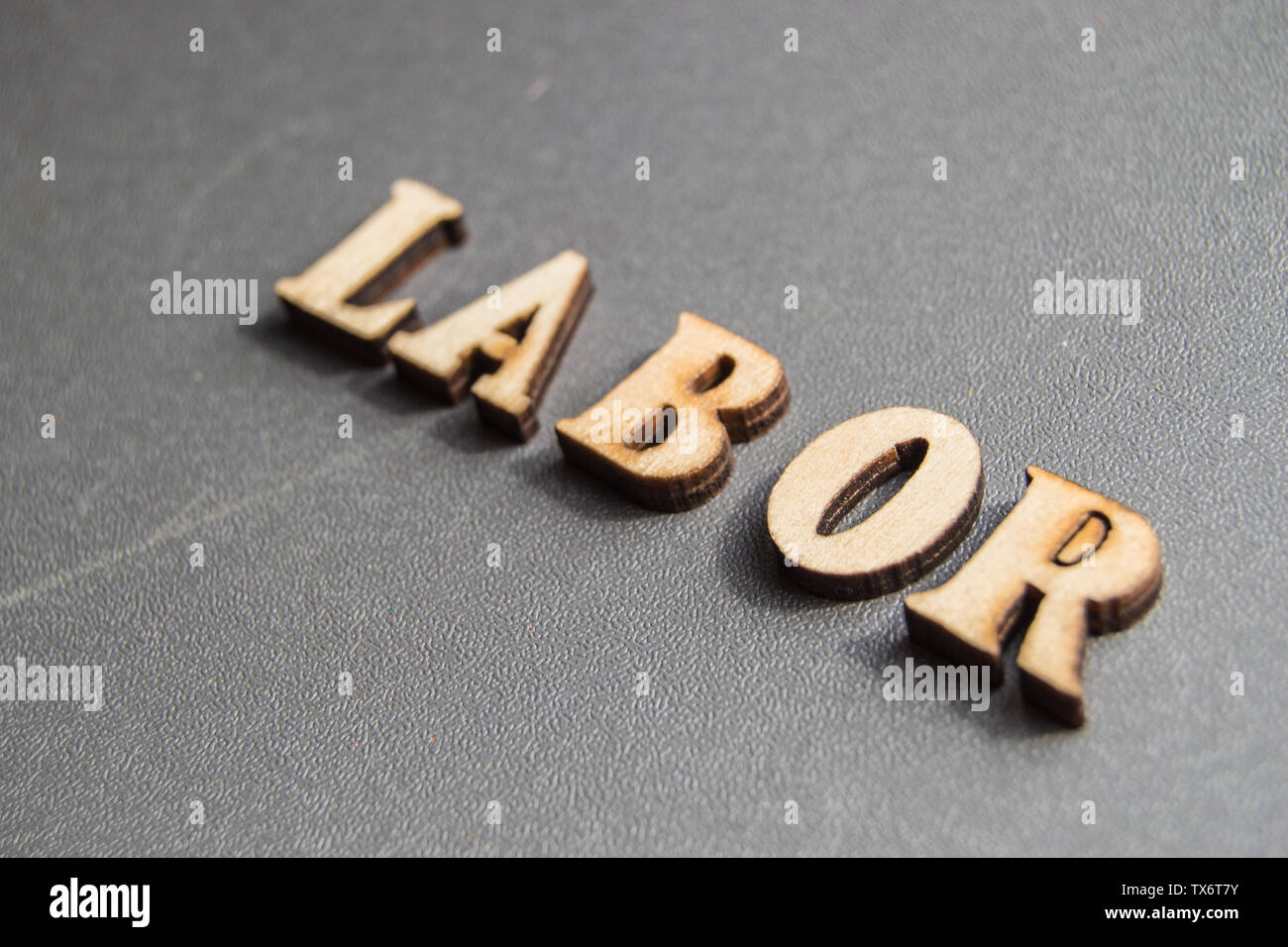Word labor on gray background with copy space and space for text, wooden vintage letters. - Stock Image