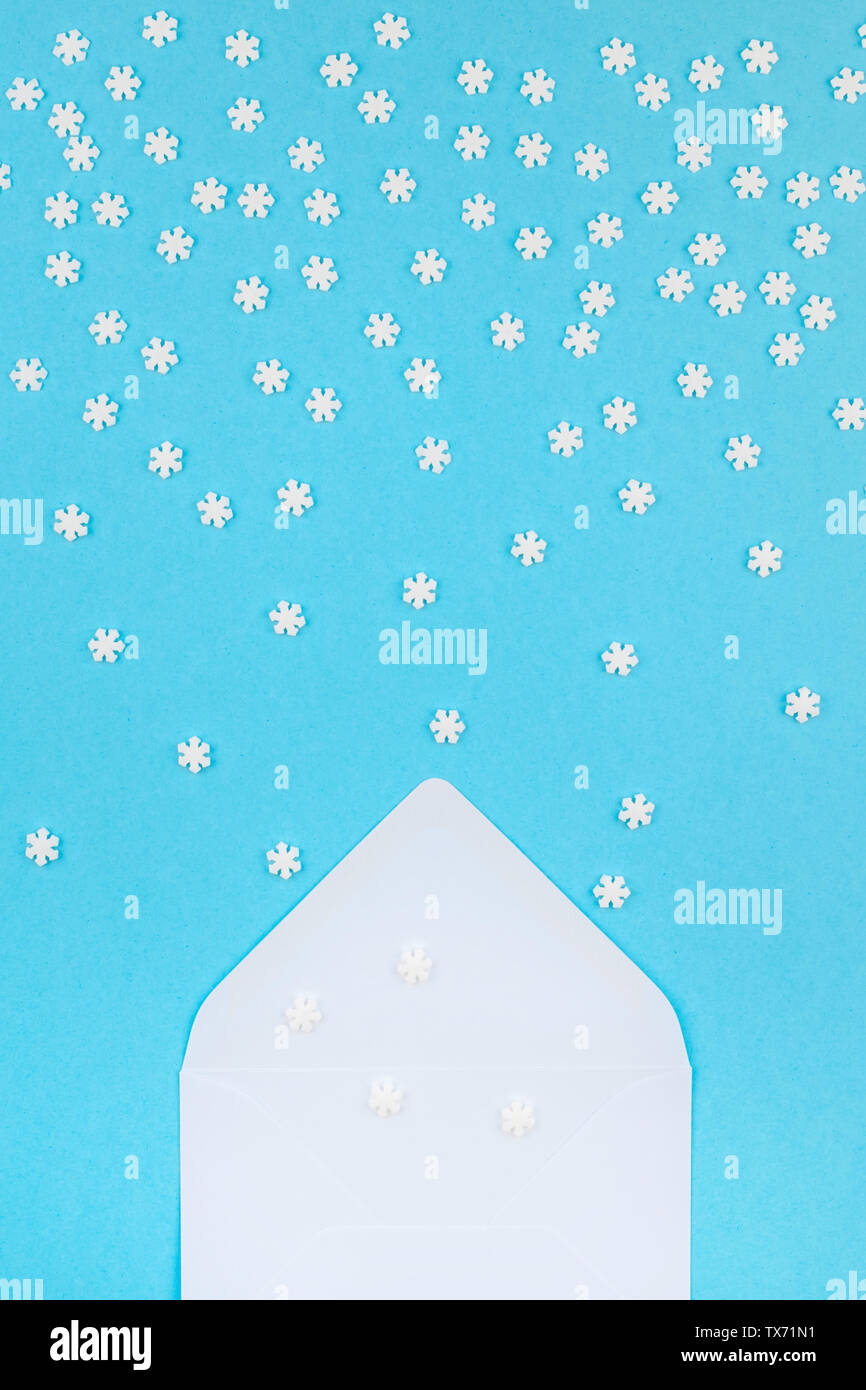 Creative Top view flat lay winter frame. Concept Mockup pattern made of small white snowflakes letter envelope pastel blue background copy space minim - Stock Image
