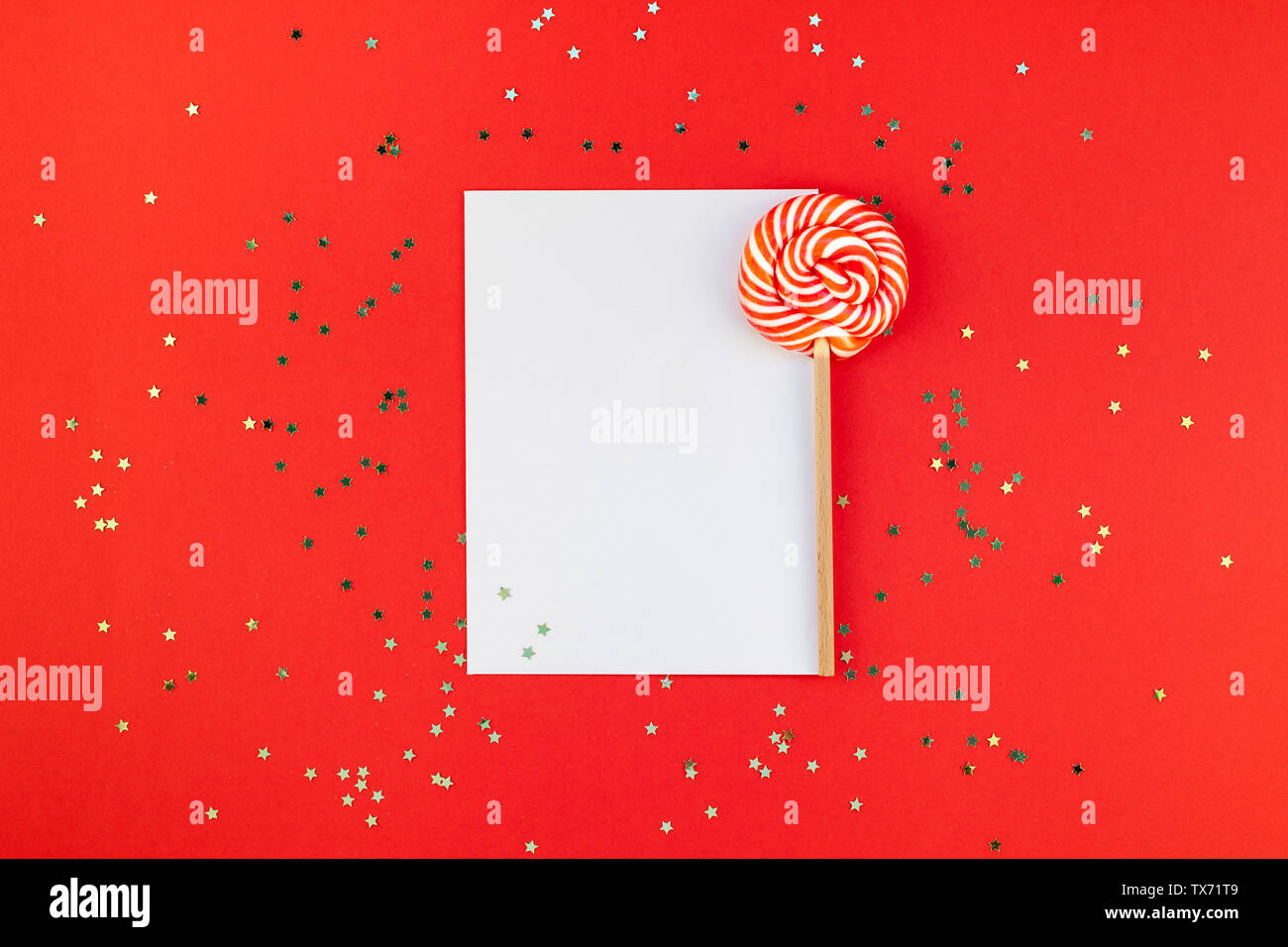 Creative New Year or Christmas greetings letter mockup flat lay top view Xmas holiday celebration envelope on red paper background golden glitter. Tem - Stock Image