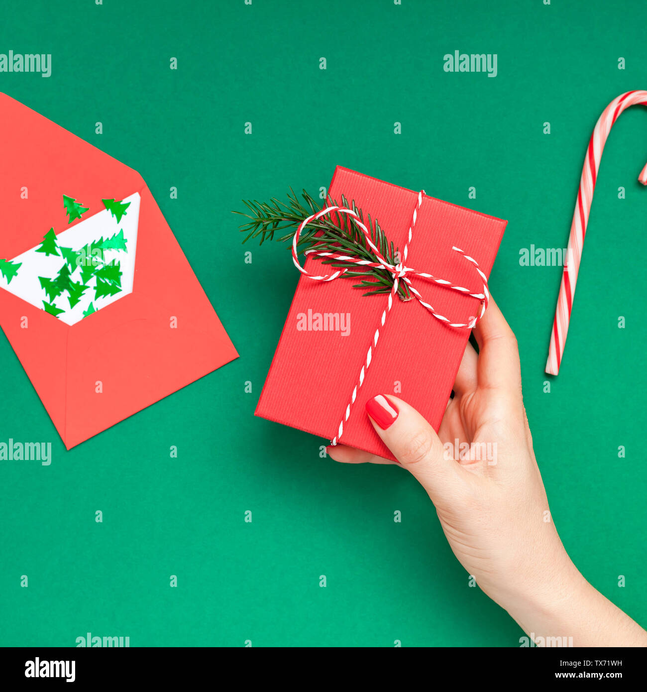 New Year or Christmas top view Xmas holiday celebration woman hand red manicure holding present gift box copy space green color paper background. Squa - Stock Image