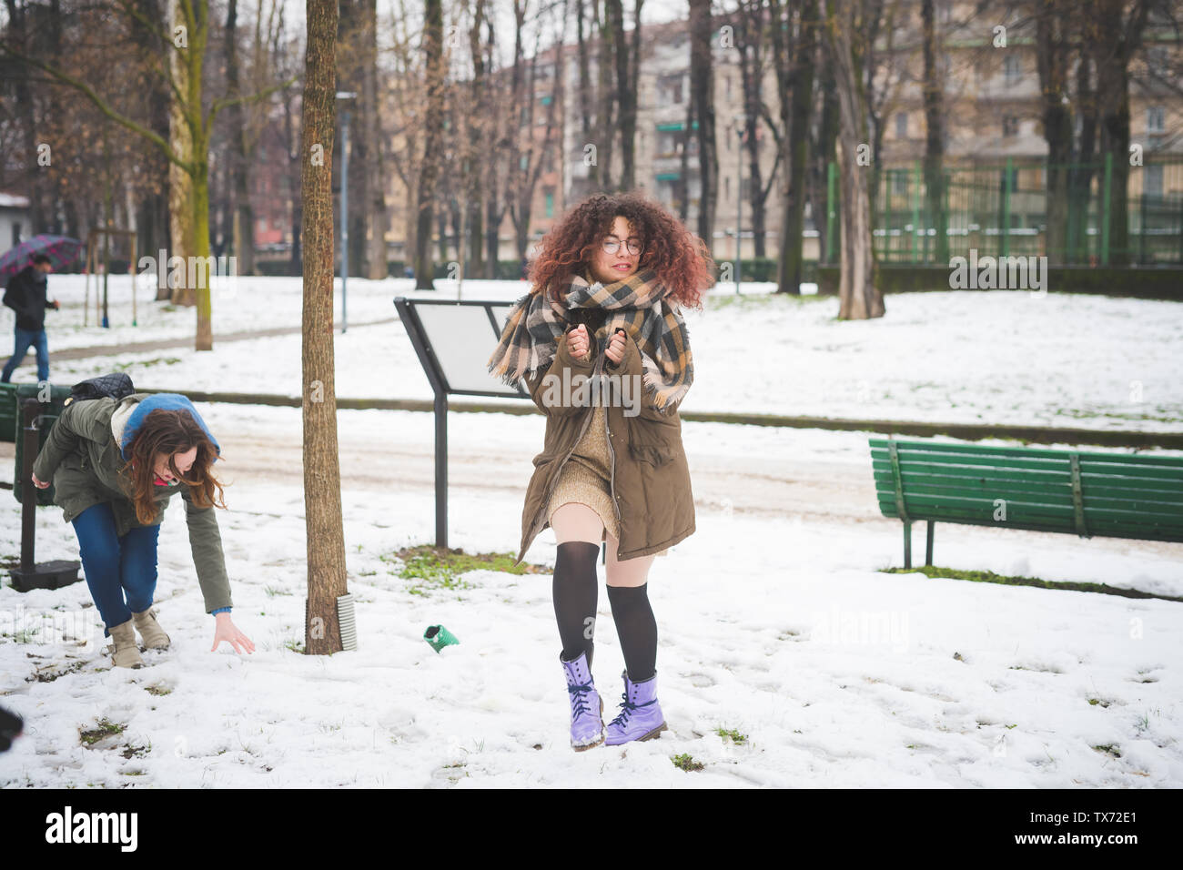two young women playing in park with snow – day off, relationship, fun - Stock Image