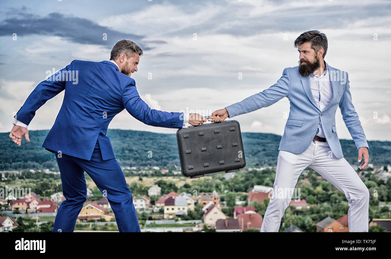 Fraud and extortion concept. Rascal racketeer extortionist cheating handover. Men suits handover briefcase. Business deal landscape background. Businessman takes away briefcase from business partner. - Stock Image