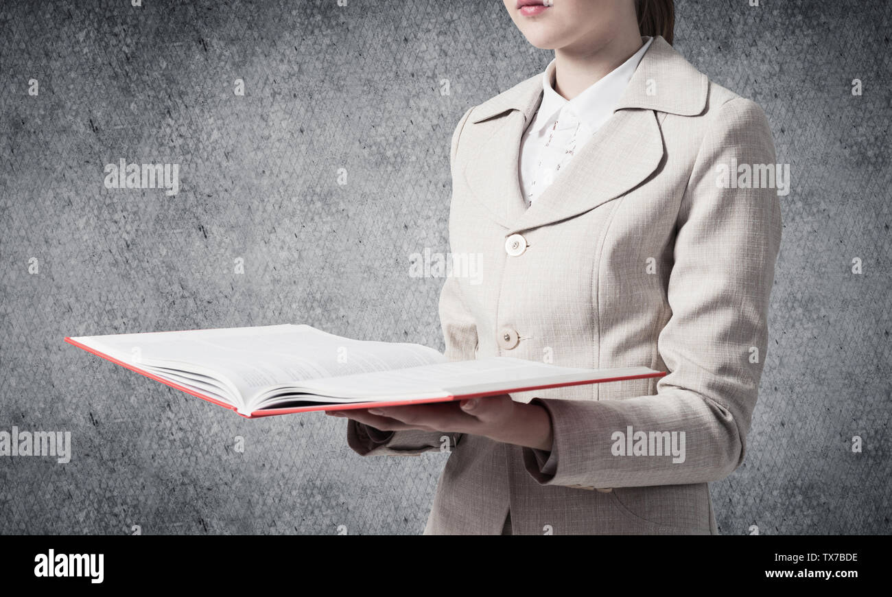 Business woman holding open book on background of grey wall. Business knowledges and education concept. Closeup open book with red cover in female han - Stock Image