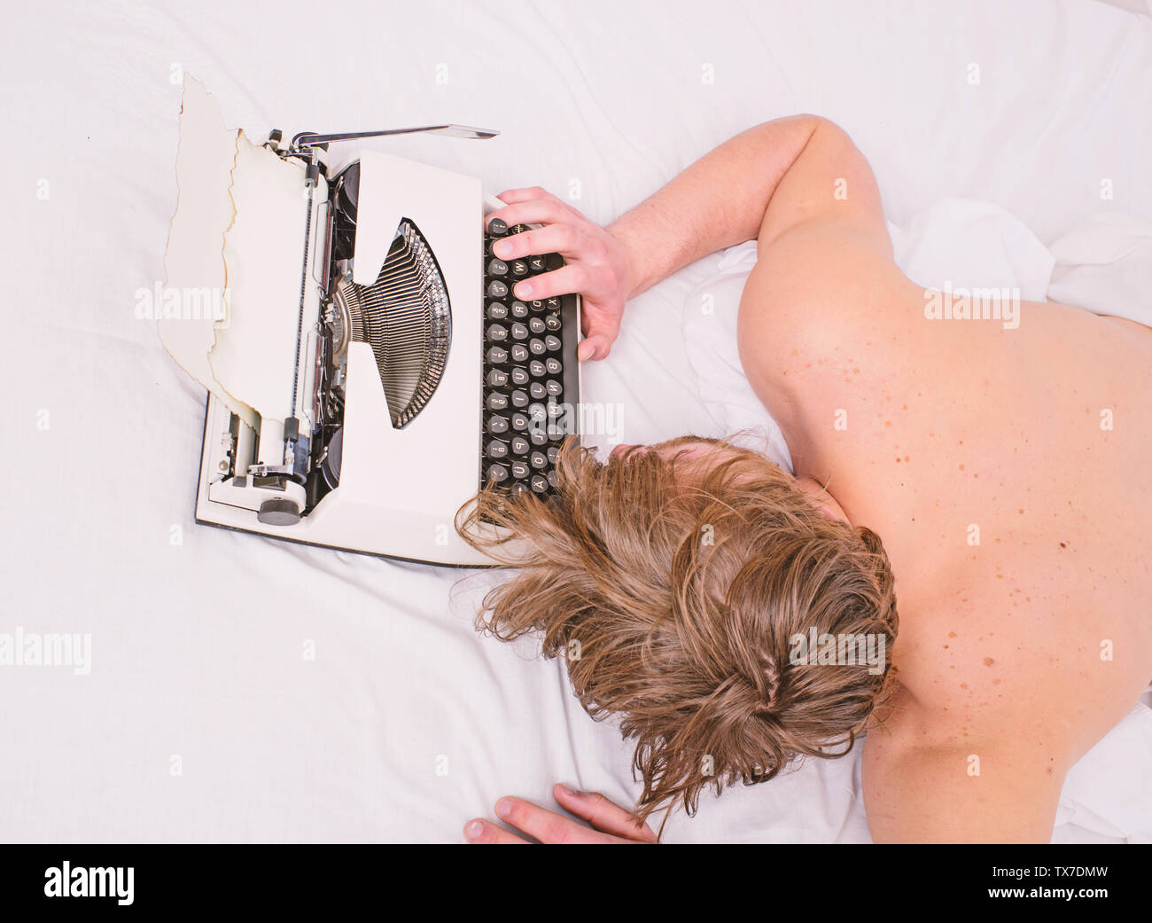 Man sleepy lay bedclothes while work. Writer used old fashioned typewriter. Exhausting occupation. Author tousled hair fall asleep while write book. Workaholic fall asleep. Man with typewriter sleep. - Stock Image